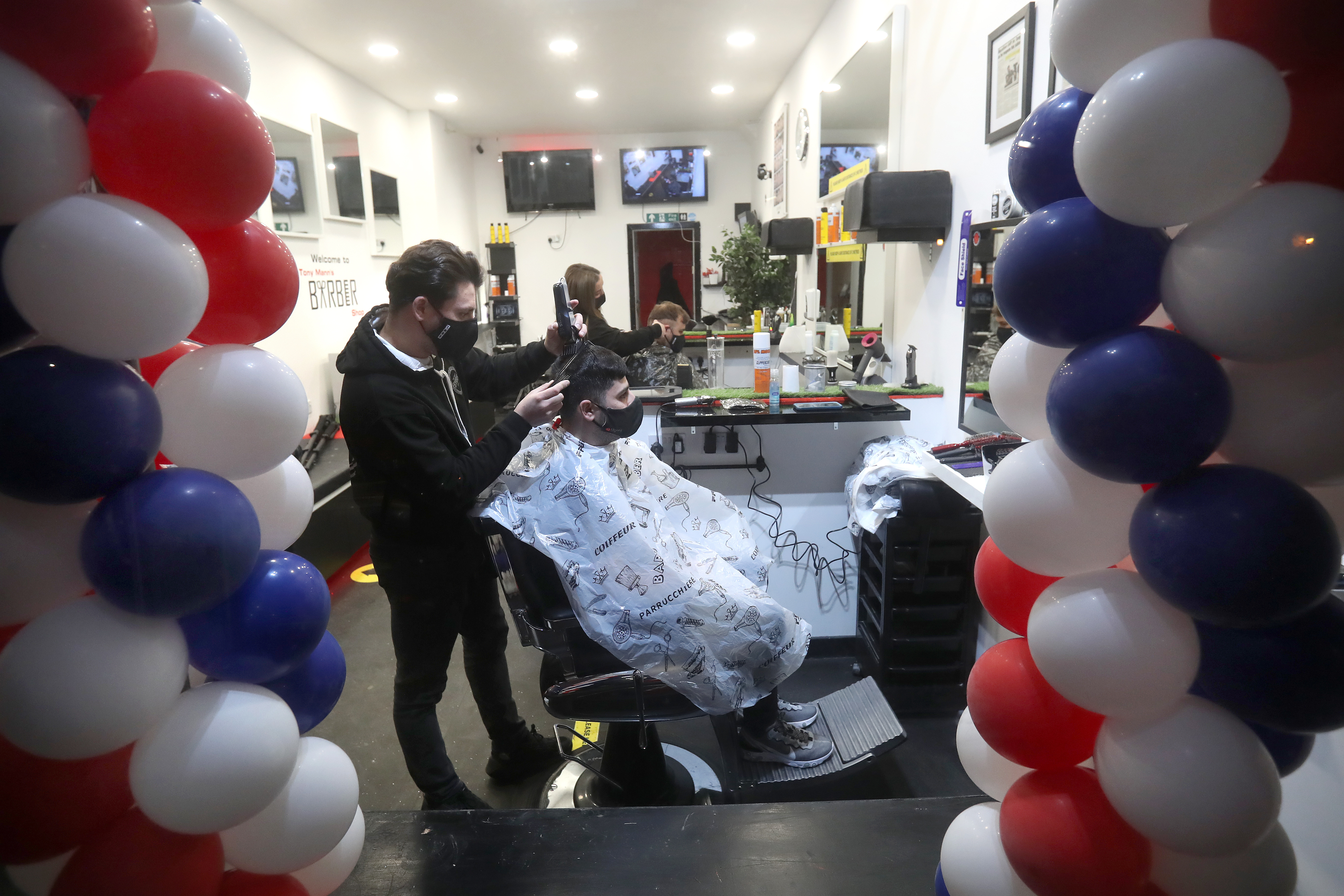 <p>Barber Tony Mann trims Max Mann's hair at Tony Mann's Barber Shop in Giffnock near Glasgow as barbers reopen across Scotland. Picture date: Monday April 5, 2021.</p>