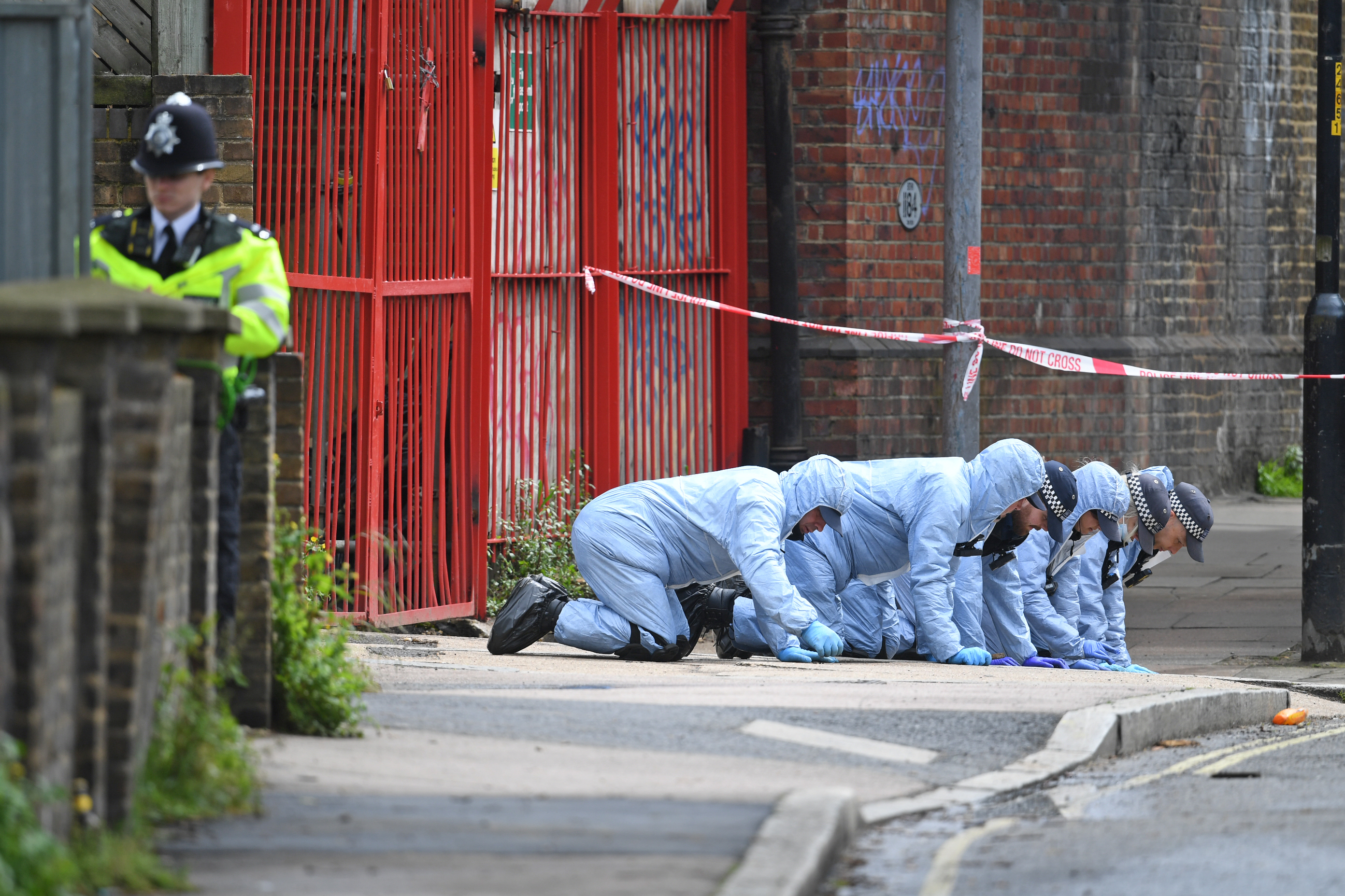 <p>Police forensic officers search a street in Peckham, southeast London, close to where black equal rights activist and mother-of-three Sasha Johnson was shot in the head during the early hours of Sunday. Picture date: Monday May 24, 2021.</p>