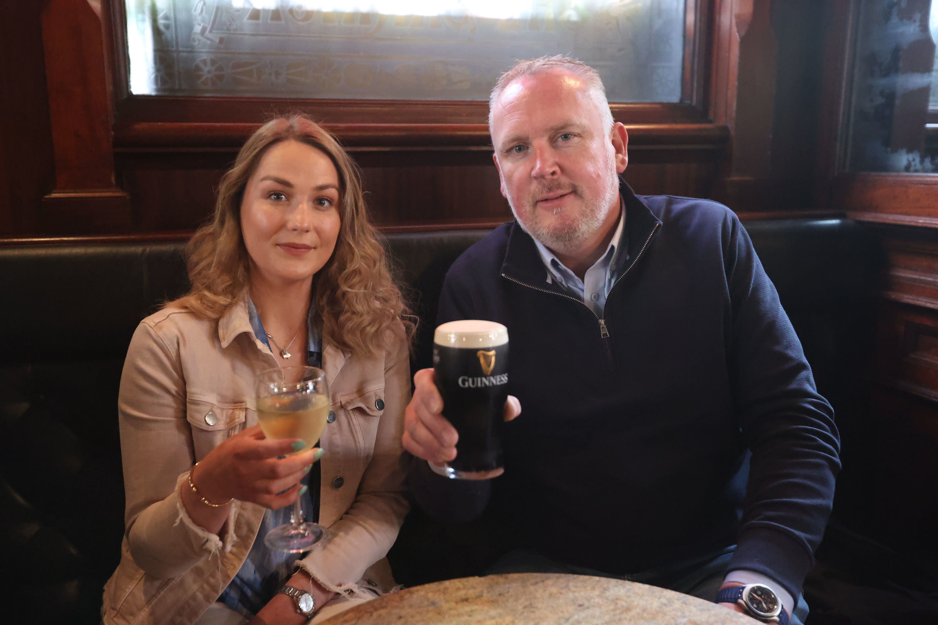<p>Natalie Knox and Campbell Brady enjoy a drink at The Garrick Bar in Belfast, after the latest easing of the Covid-19 rules in Northern Ireland .</p>