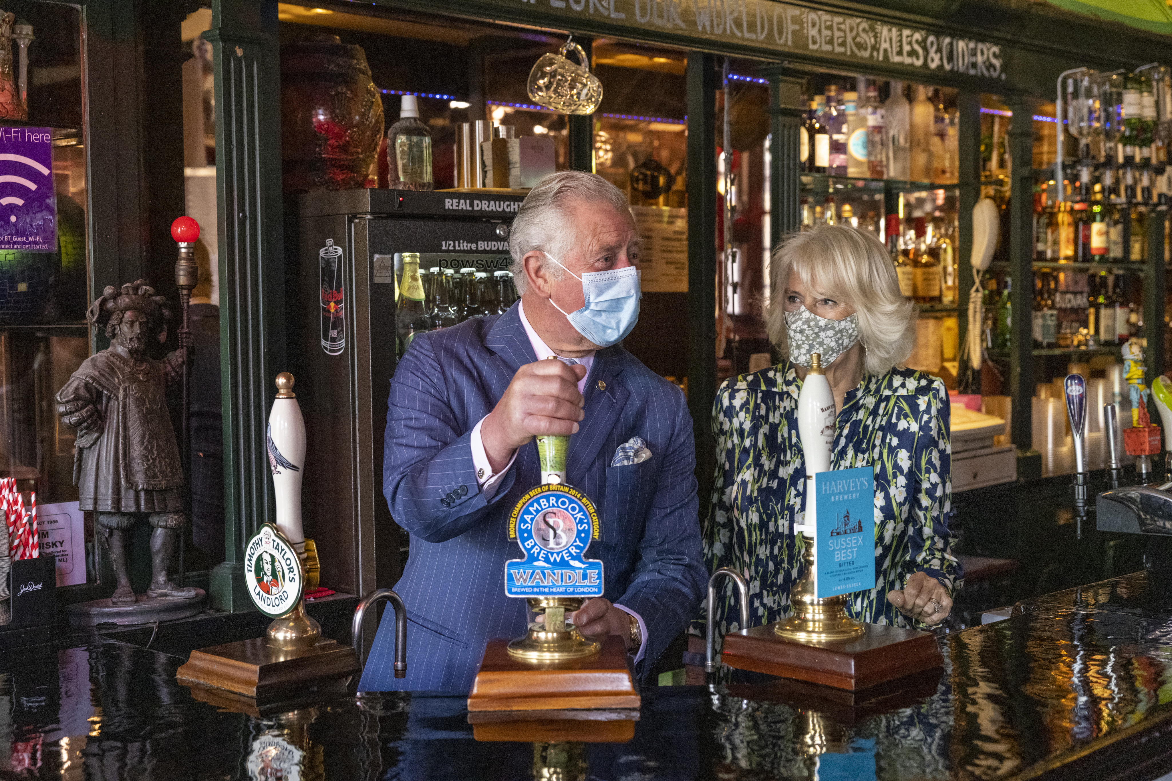 <p>The Duchess of Cornwall looks on as the Prince of Wales pours a pint in the Prince of Wales public house, during a visit to Clapham Old Town, south London, to celebrate the high street and retail sector as non-essential shops re-open and Coronavirus restrictions ease. Picture date: Thursday May 27, 2021.</p>