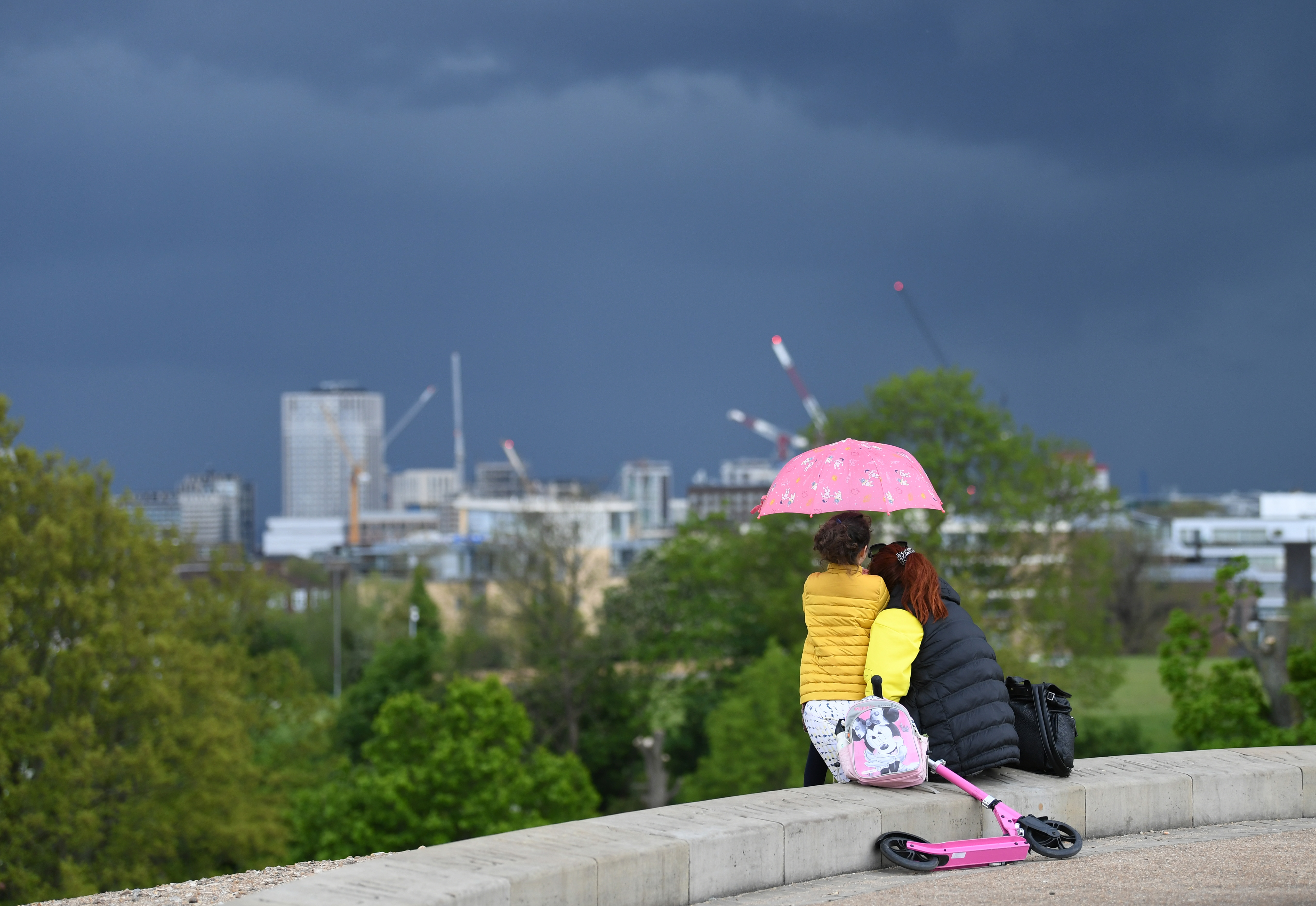 <p>People looking at storm clouds over London from Primrose Hill. Picture date: Tuesday May 18, 2021.</p>
