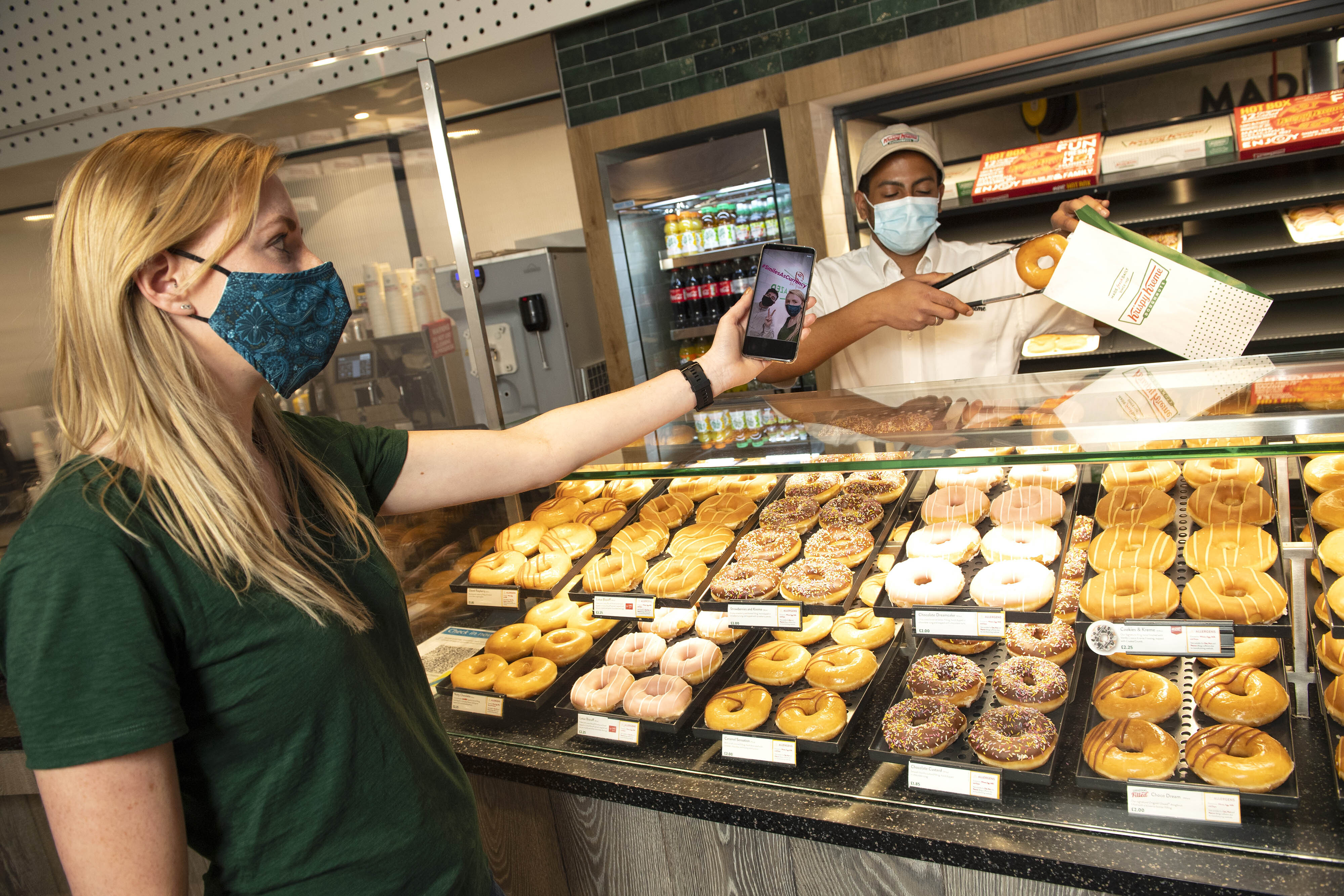 <p>EDITORIAL USE ONLY Customer, Rachel picks up a free Original Glazed doughnut in exchange for showing the #SmilesAsCurrency at Krispy Kreme in Stratford, London as part of their giveaway to celebrate the easing of lockdown. Issue date: Monday May 10, 2021.</p>