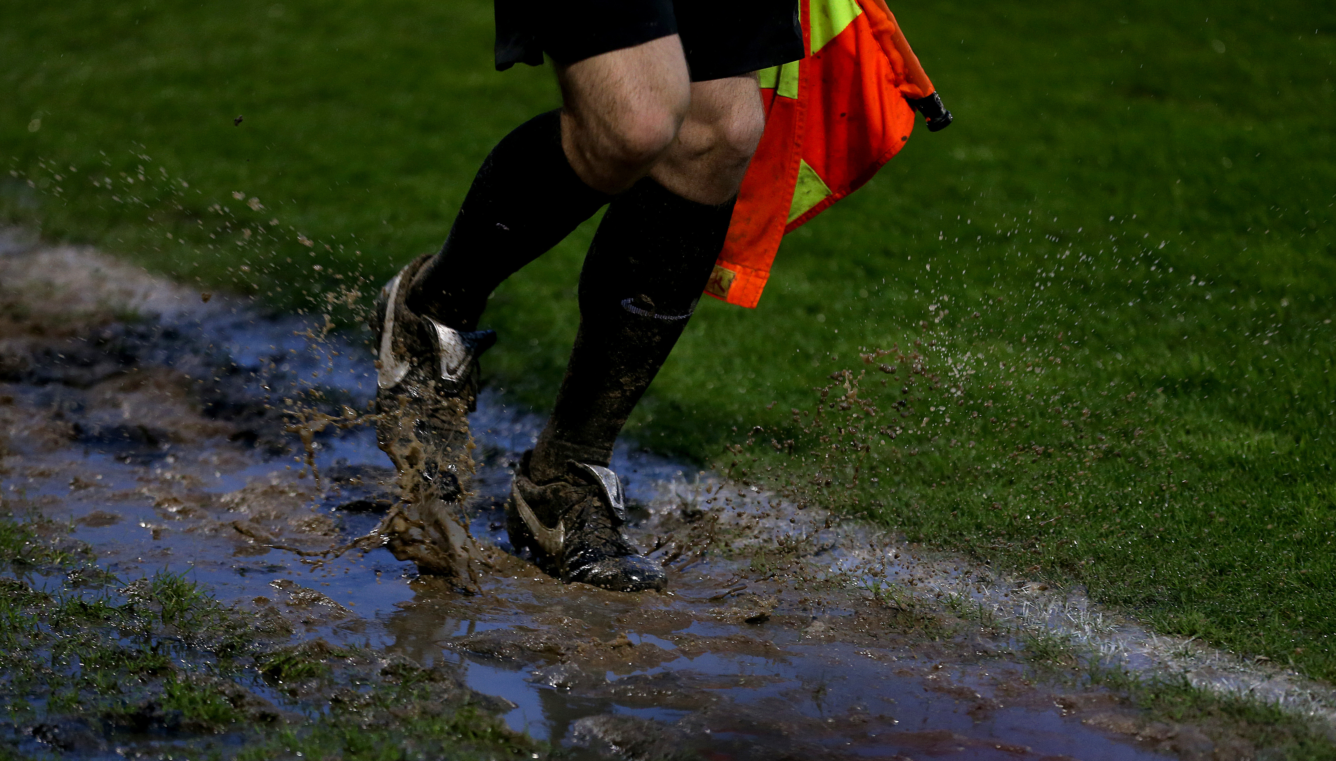 <p>Assistant referee running though mud on the touchline during the Sky Bet League Two semi final, second leg match at The New Lawn Stadium, Nailsworth. Picture date: Sunday May 23, 2021.</p>