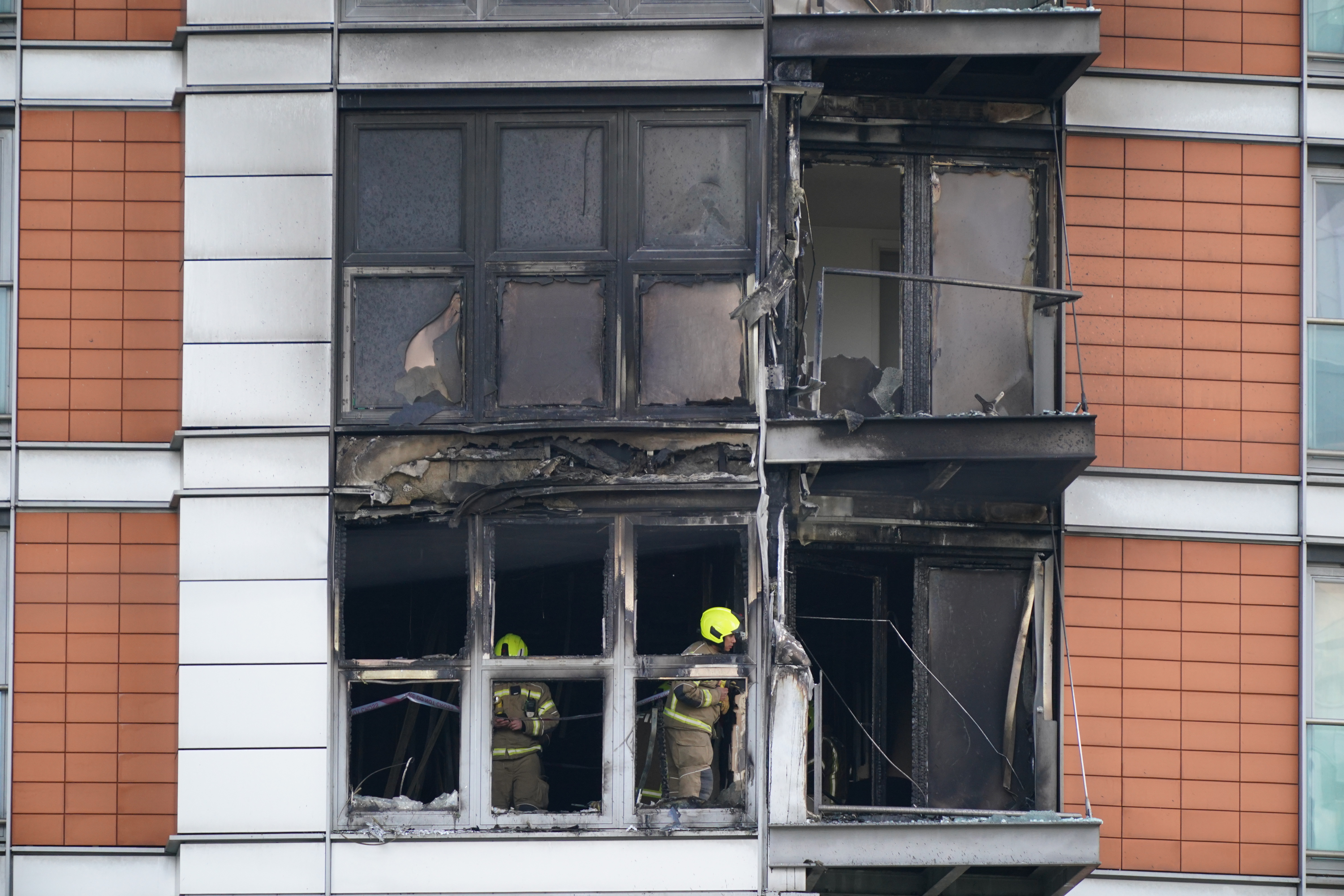 <p>Firefighters inspect damage to a 19-storey tower block in New Providence Wharf in London, where the London Fire Brigade (LFB) was called to on Friday morning to reports of a fire and more than 100 firefighters are tackling a blaze that has ripped through the block, believed to be covered in cladding, in east London. Picture date: Friday May 7, 2021. See PA story FIRE CanaryWharf. Photo credit should read: Yui Mok/PA</p>