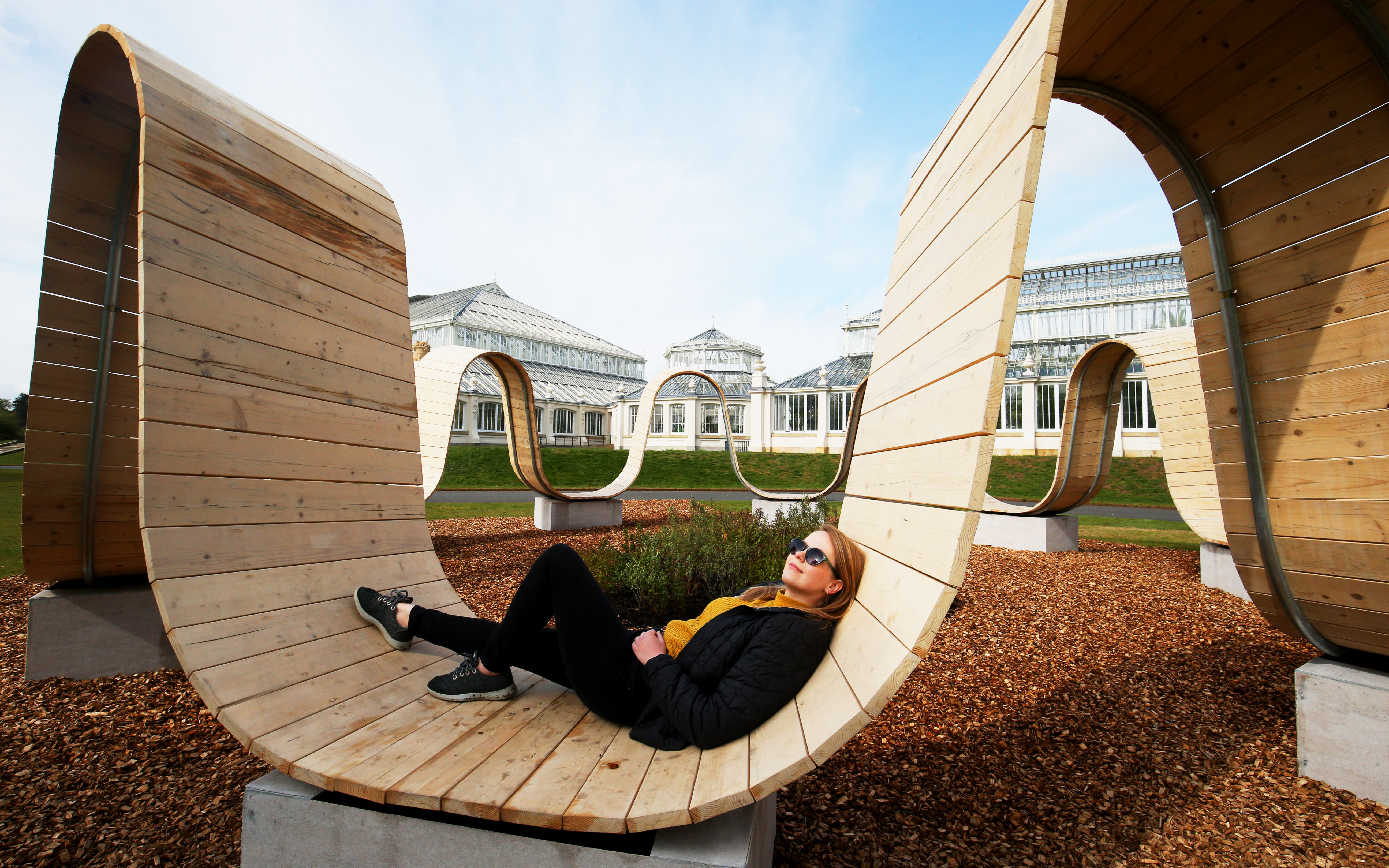 <p>Visitor programme manager Kate Solecki rests on a portion of the Paul Cocksedge 2019 London Design Festival piece 'Please Be Seated' at the new visitor attraction Secret World of Plants at Kew Gardens, London, which runs from May 1st to September 19th, 2021. Picture date: Thursday May 6, 2021.</p>