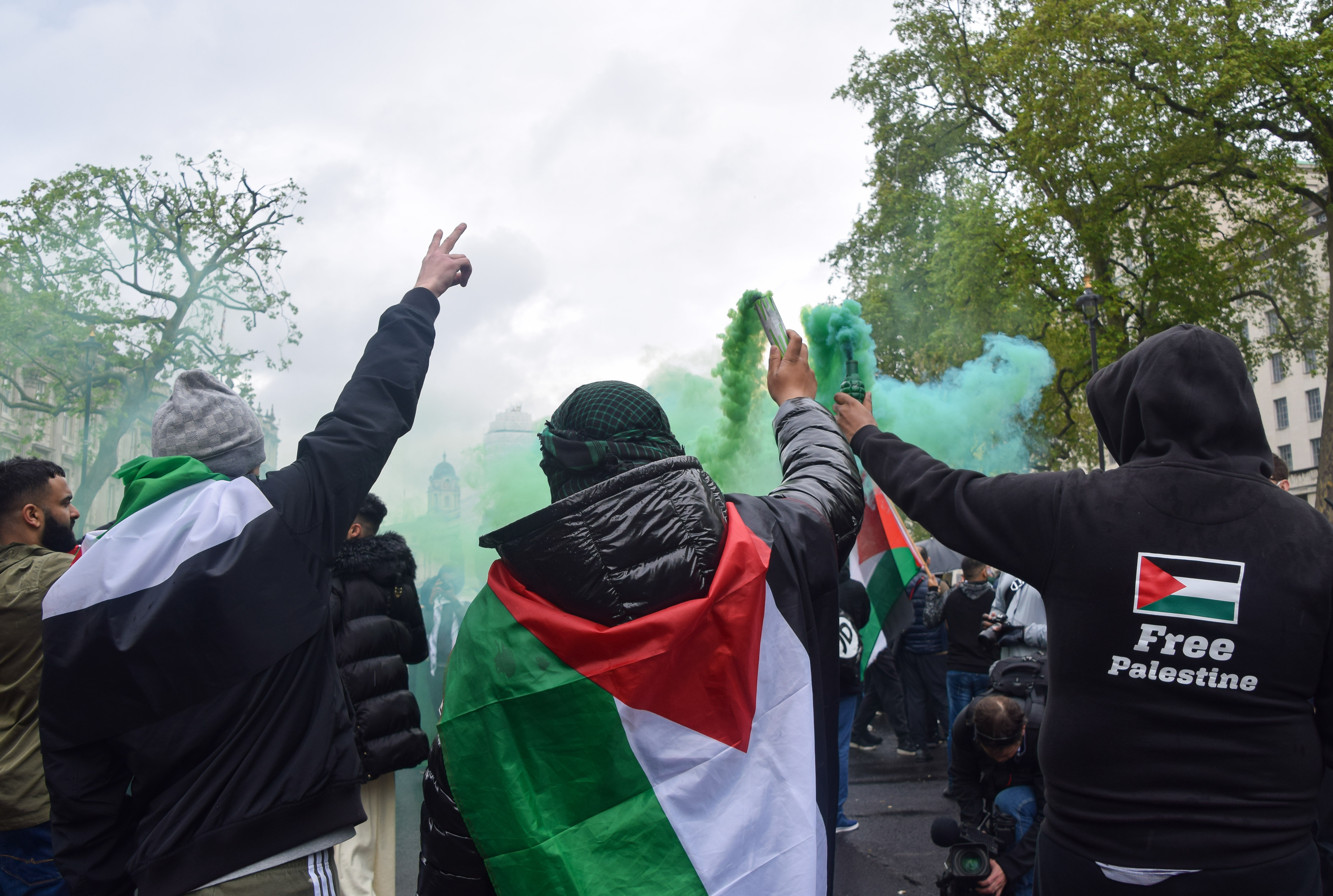 <p>LONDON, UNITED KINGDOM - 2021/05/16: Protesters hold up smoke flares outside Downing Street during the pro-Palestine demonstration. Protesters gathered in Central London for the second day of the weekend in support of Palestine as tensions between Israel and Palestine escalate. (Photo by Vuk Valcic/SOPA Images/LightRocket via Getty Images)</p>