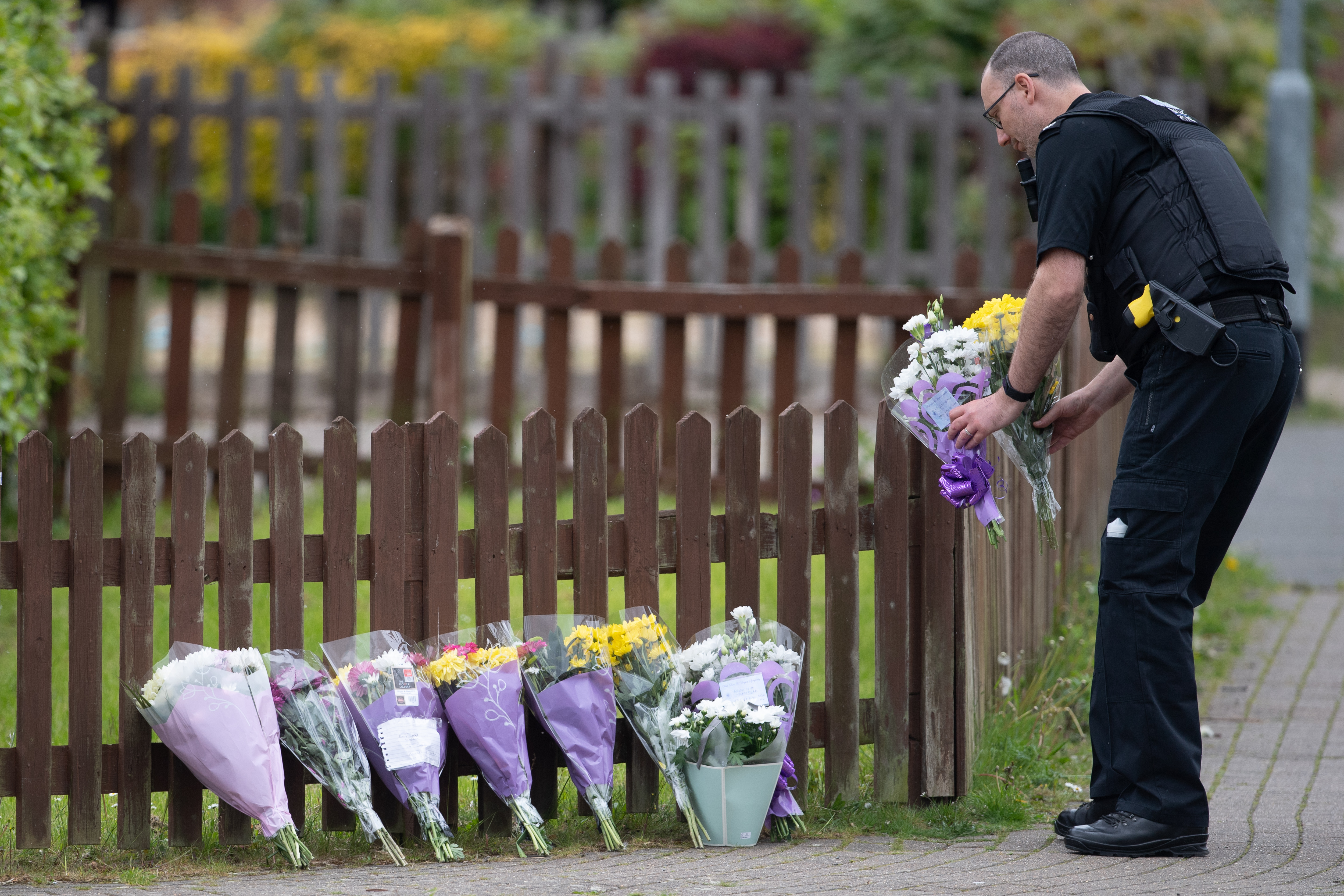 <p>A police officer carries flowers near the scene in Constable Road, Corby, Northamptonshire, following the fatal stabbing of a 16-year-old boy on Tuesday. Picture date: Wednesday May 26, 2021.</p>
