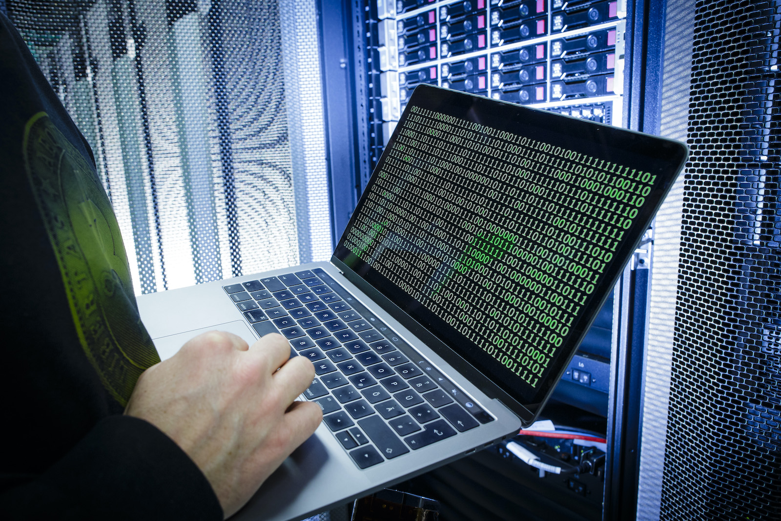 BERLIN, GERMANY - JANUARY 12: Symbolic photo with topic online crime, data theft and piracy: A man poses with a laptop showing a binary code in front of Server racks in a server center on January 12, 2018, in Berlin, Germany. (Photo Illustration by Thomas Trutschel/Photothek via Getty Images)