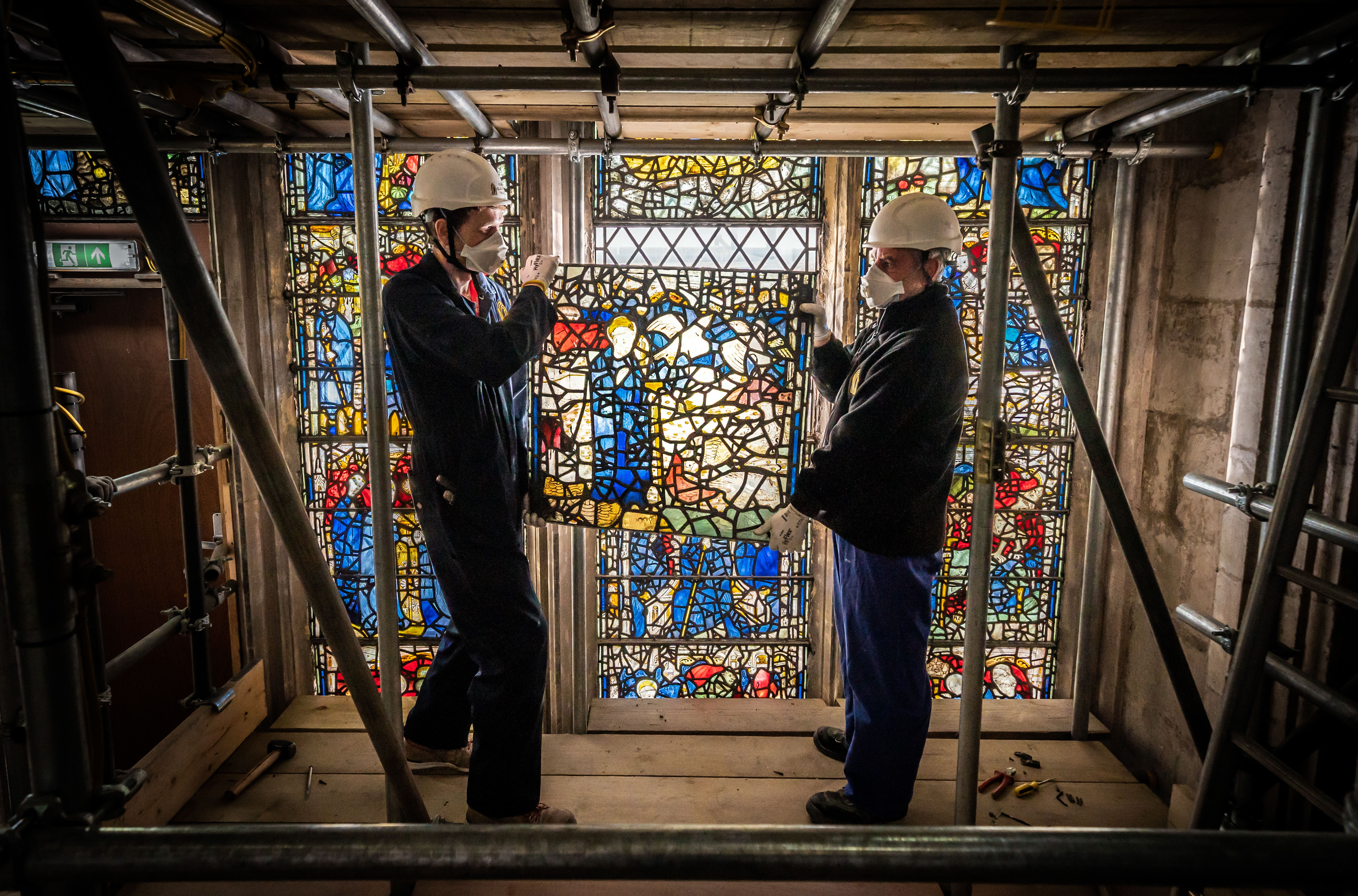 <p>Conservator Matthew Nickels (left) and Master Glazier Tony Cattle (right) from York Glaziers Trust removed a stained glass window panel at the start of a new five year, �5m project to conserve York Minster's South East Transept and its medieval St Cuthbert Window. Picture date: Tuesday May 25, 2021. Work is being undertaken by York Glaziers Trust to remove stained glass panels from the window, which is nearly 600-years-old and one of the largest surviving narrative windows in the world. The project involves major conservation and restoration works to both the stained glass and stone elements of the window and the South East Transept in which the window sits.</p>