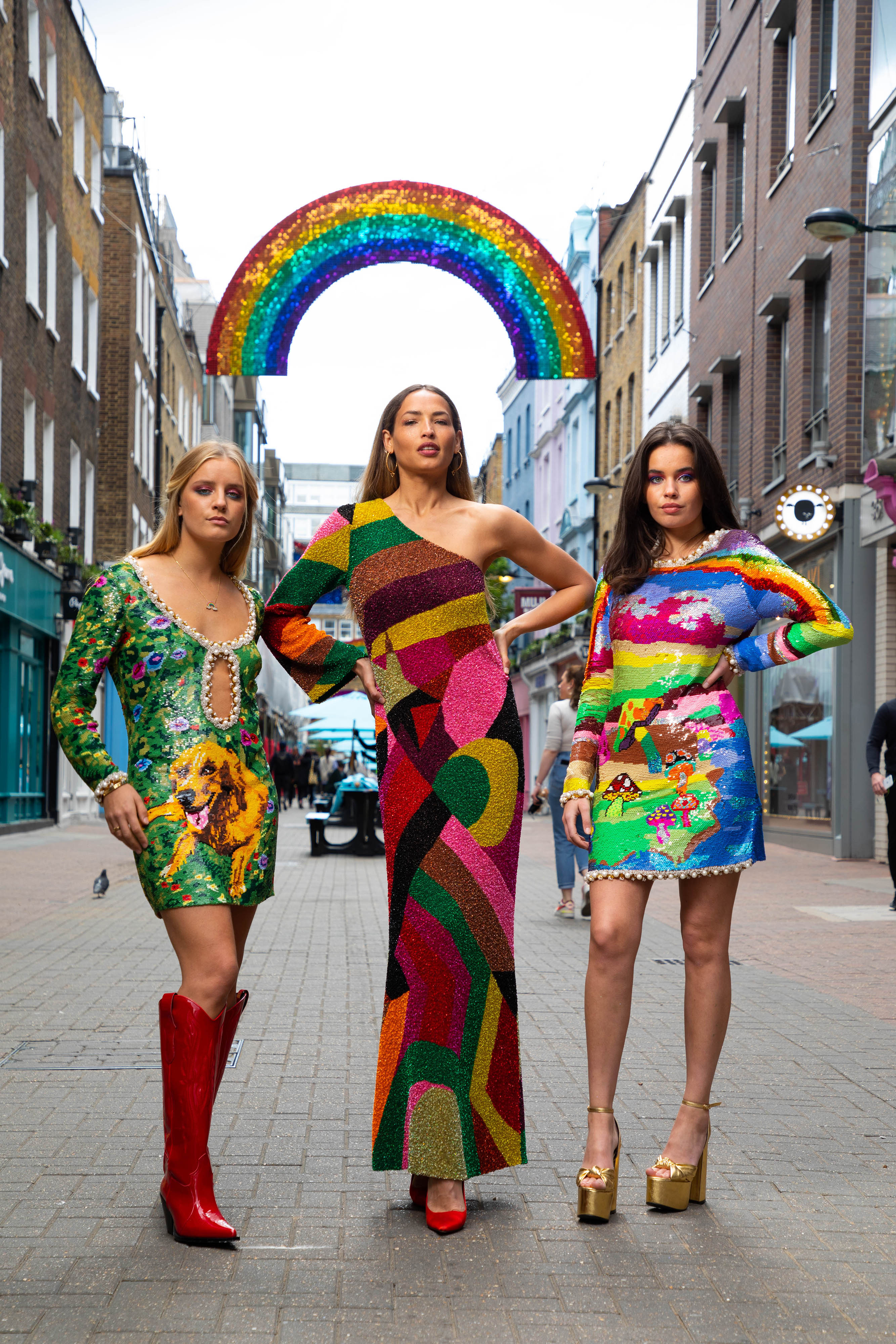 <p>EDITORIAL USE ONLY (Left to right) Krizzy Doble, Charlotte Carter-Allen and Izzy Henry at the unveiling of the brand-new rainbow installation in Carnaby, featuring two bright shimmer disk rainbows arching over Carnaby Street, London. Picture date: Wednesday May 12, 2021.</p>