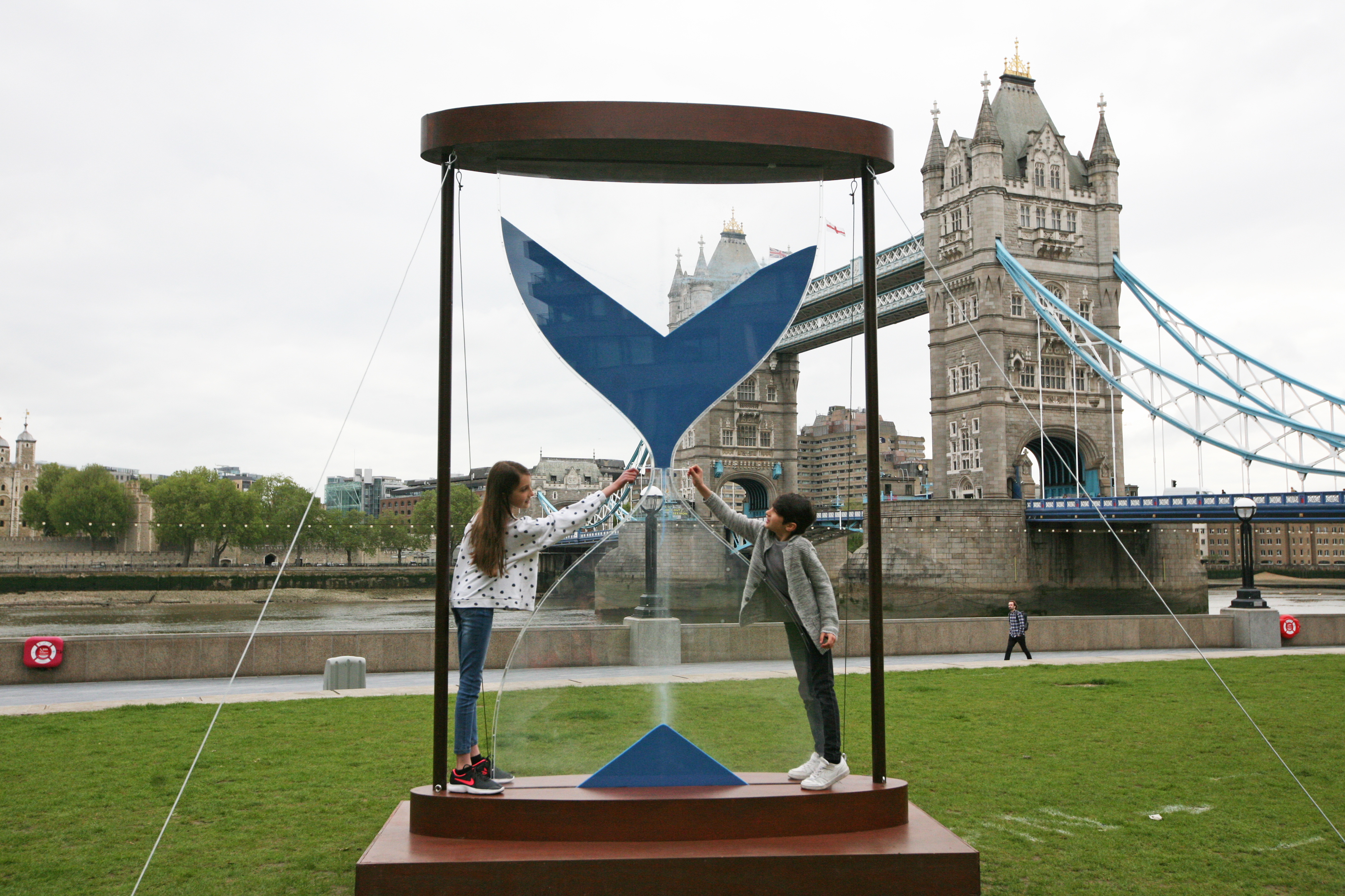 <p>Amelia, aged 9, and Joshua, aged 6, interact with a 3.5 metre hourglass in Potter's Field, London, by clean water charity WaterAid ahead of the G7 leaders' summit in June that illustrates the urgency of the climate crisis that is leading to more people being forced into water scarcity. Picture date: Tuesday May 25, 2021.</p>
