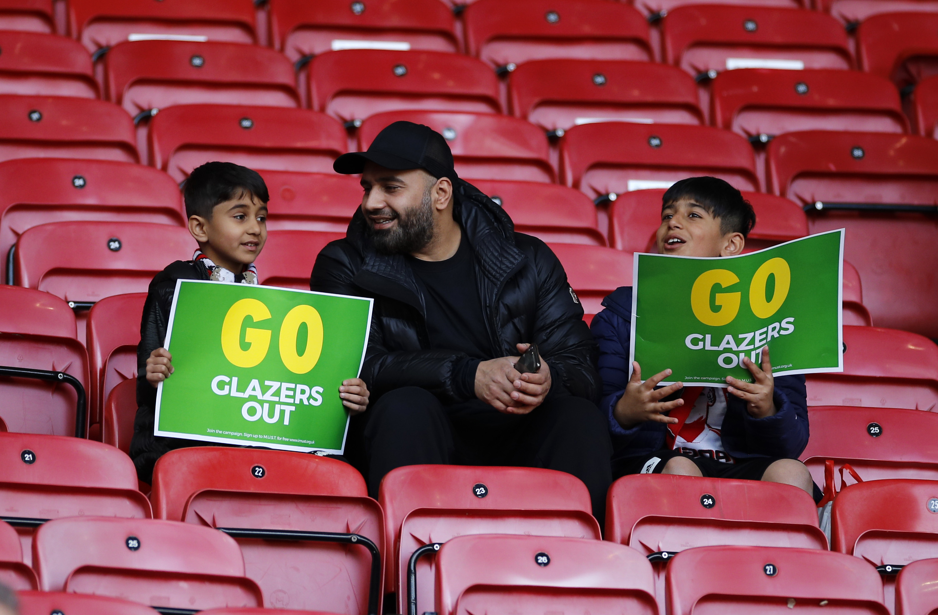 <p>MANCHESTER, ENGLAND - MAY 18: Fans of Manchester United look on from their seat inside of the stadium whilst holding a protest placard ahead of the Premier League match between Manchester United and Fulham at Old Trafford on May 18, 2021 in Manchester, England. A limited number of fans will be allowed into Premier League stadiums as Coronavirus restrictions begin to ease in the UK following the COVID-19 pandemic. (Photo by Phil Noble - Pool/Getty Images)</p>