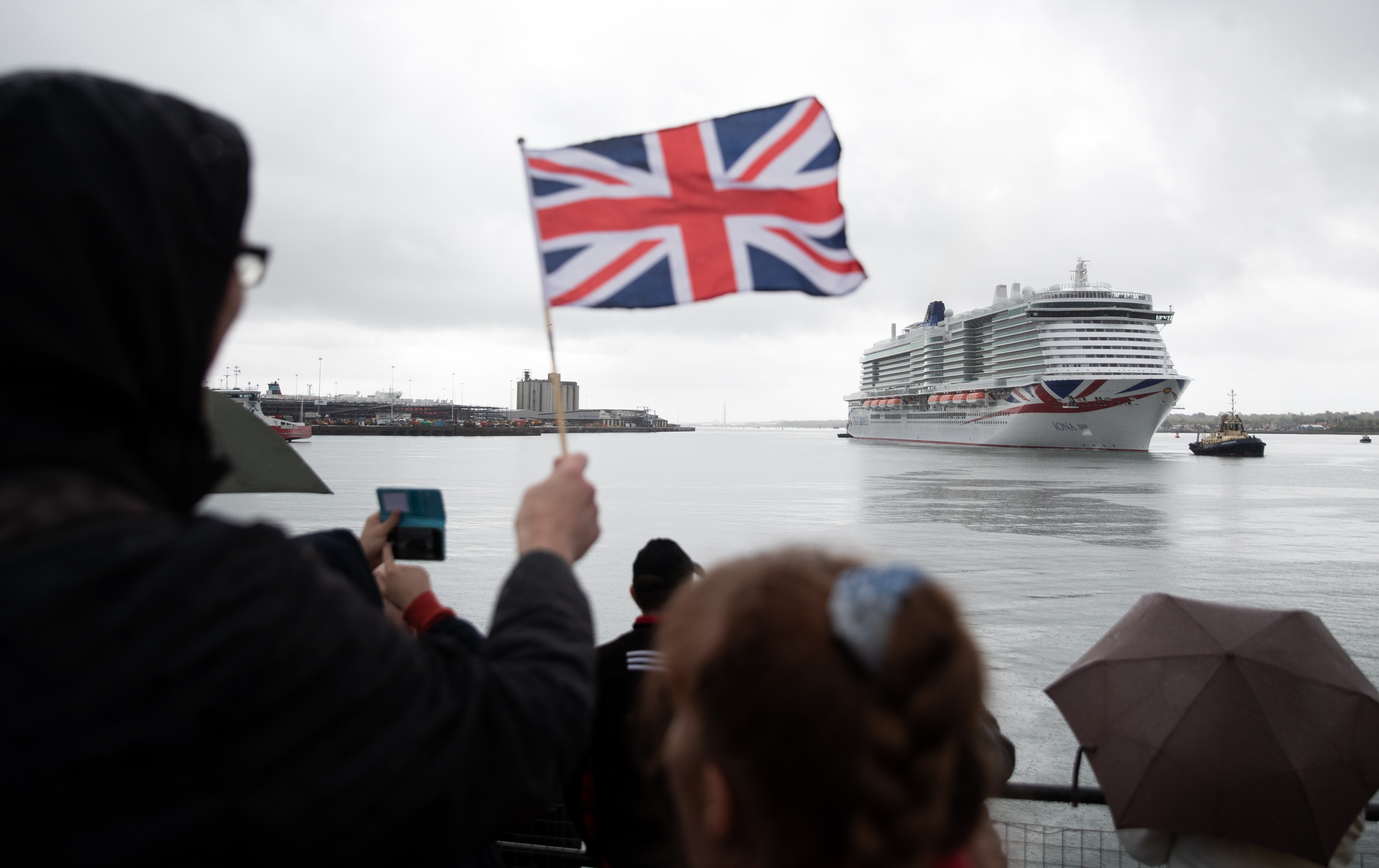 <p>A person waves a Union flag as the new P&amp;O cruise ship Iona enters Southampton for the first time ahead of its naming ceremony. Iona, the largest cruise ship built for the UK market, is 345 metres long (1,132ft), weighs 185,000 tonnes, and has 17 passenger decks, creating capacity for 5,200 holidaymakers. Picture date: Sunday May 16, 2021.</p>
