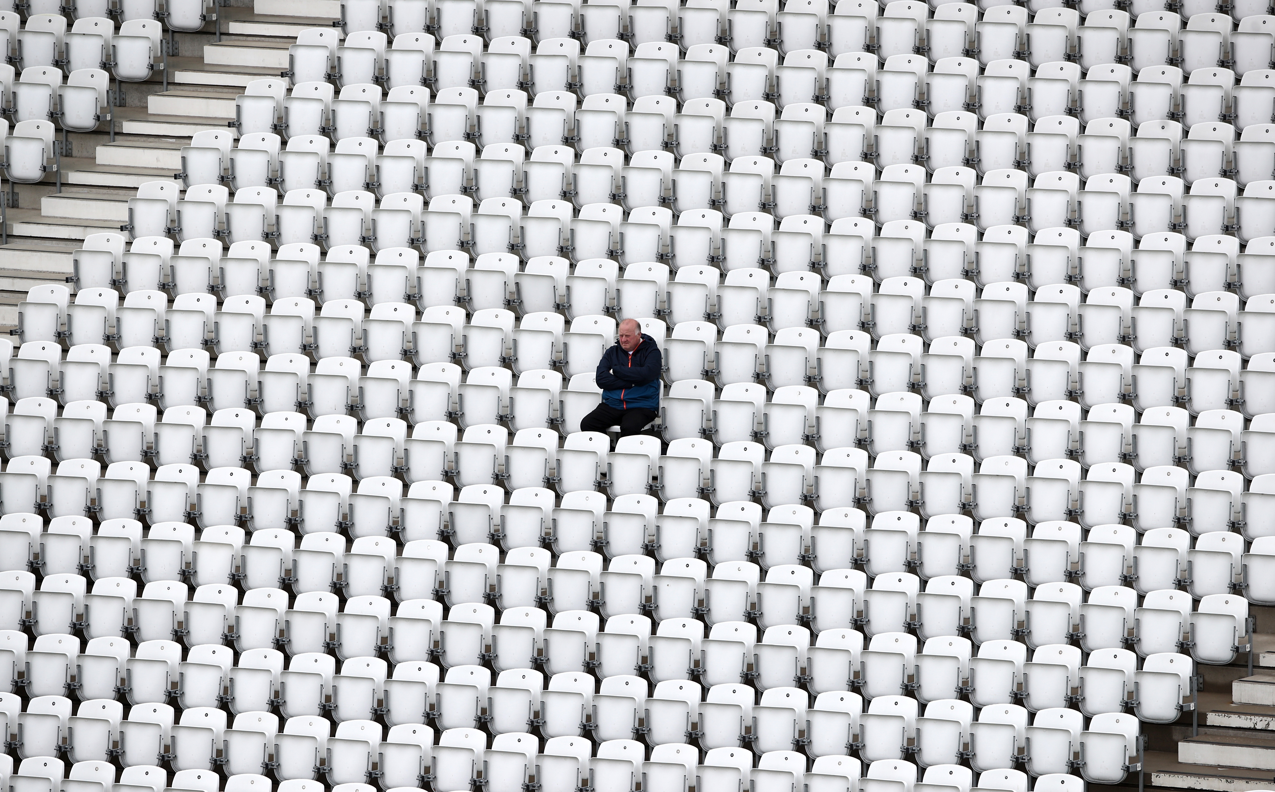 <p>A spectator waits in the stands as rain delays play during day two of the LV= Insurance County Championship match at Trent Bridge, Nottingham. Picture date: Friday May 21, 2021.</p>