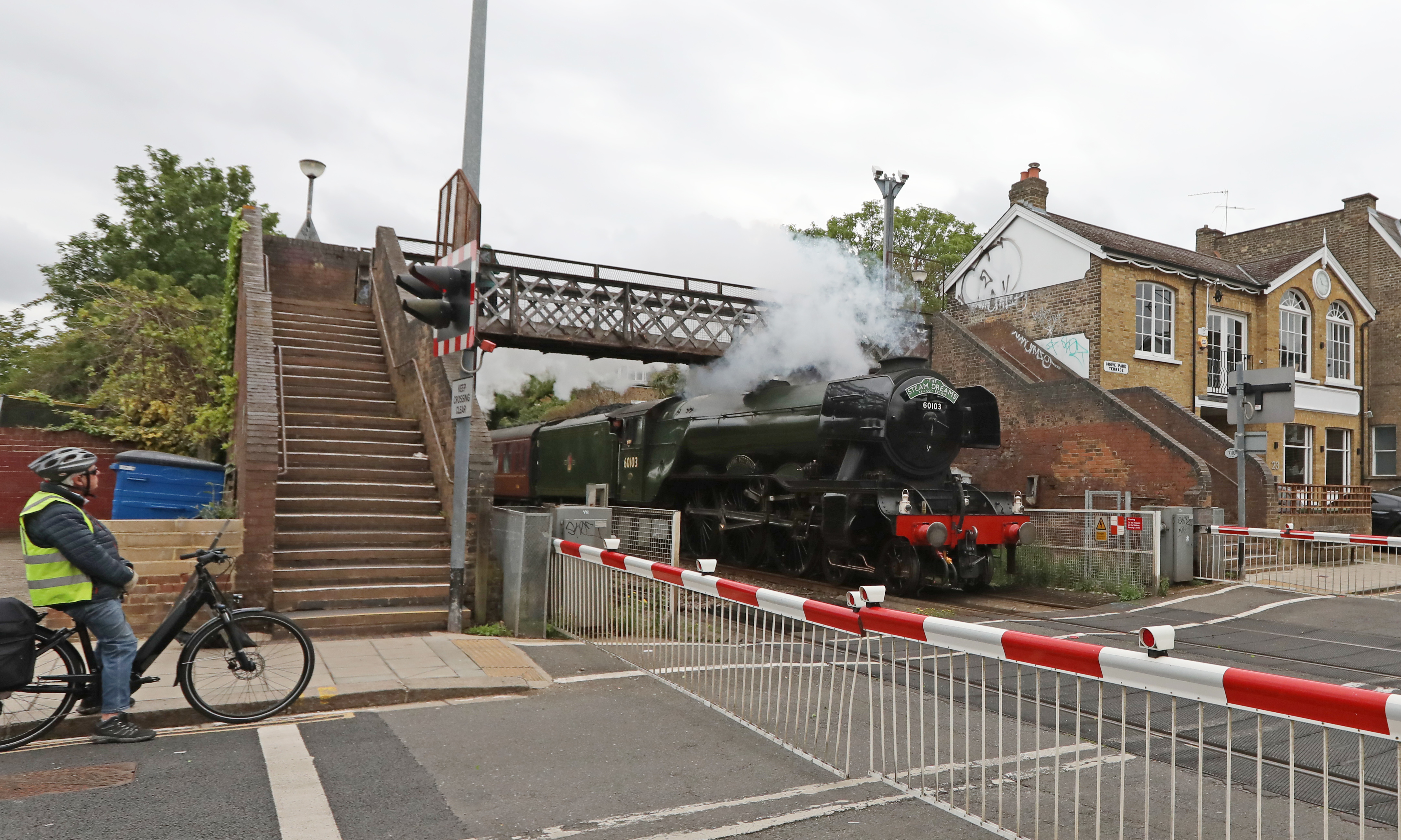 <p>The National Railway Museum's Flying Scotsman passes over a level crossing in Chiswick, west London, on its first main line trip with passengers since 2019 as part of The Steam Dreams Rail Company's series of summer trains from London Victoria Station. Picture date: Thursday May 20, 2021.</p>