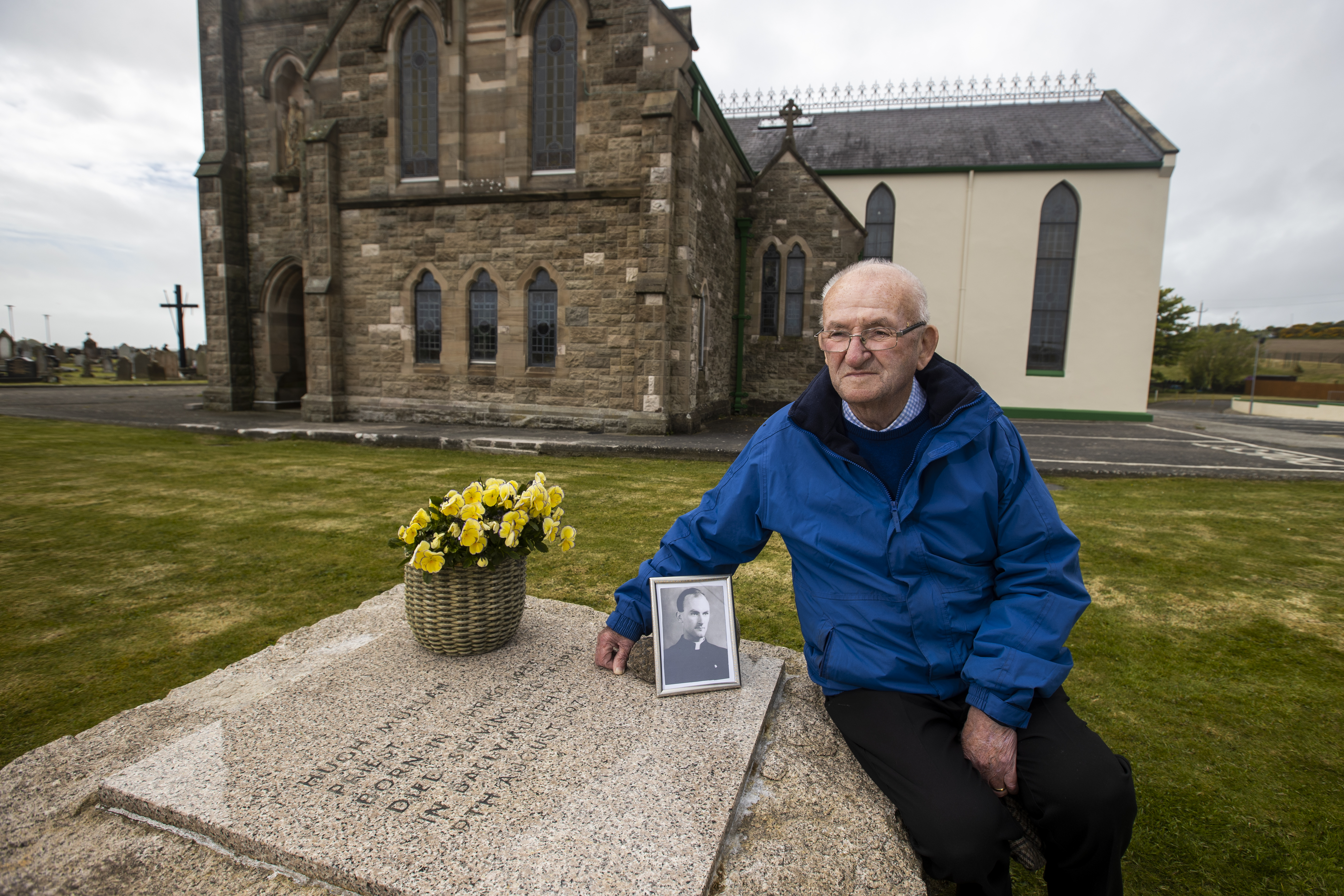 <p>Patsy Mullan, brother of Father Hugh Mullan, visit's his brother's grave at St. Patrick's Church in Portaferry, ahead of the findings tomorrow of the Ballymurphy Inquest. Picture date: Monday May 10 2021.</p>