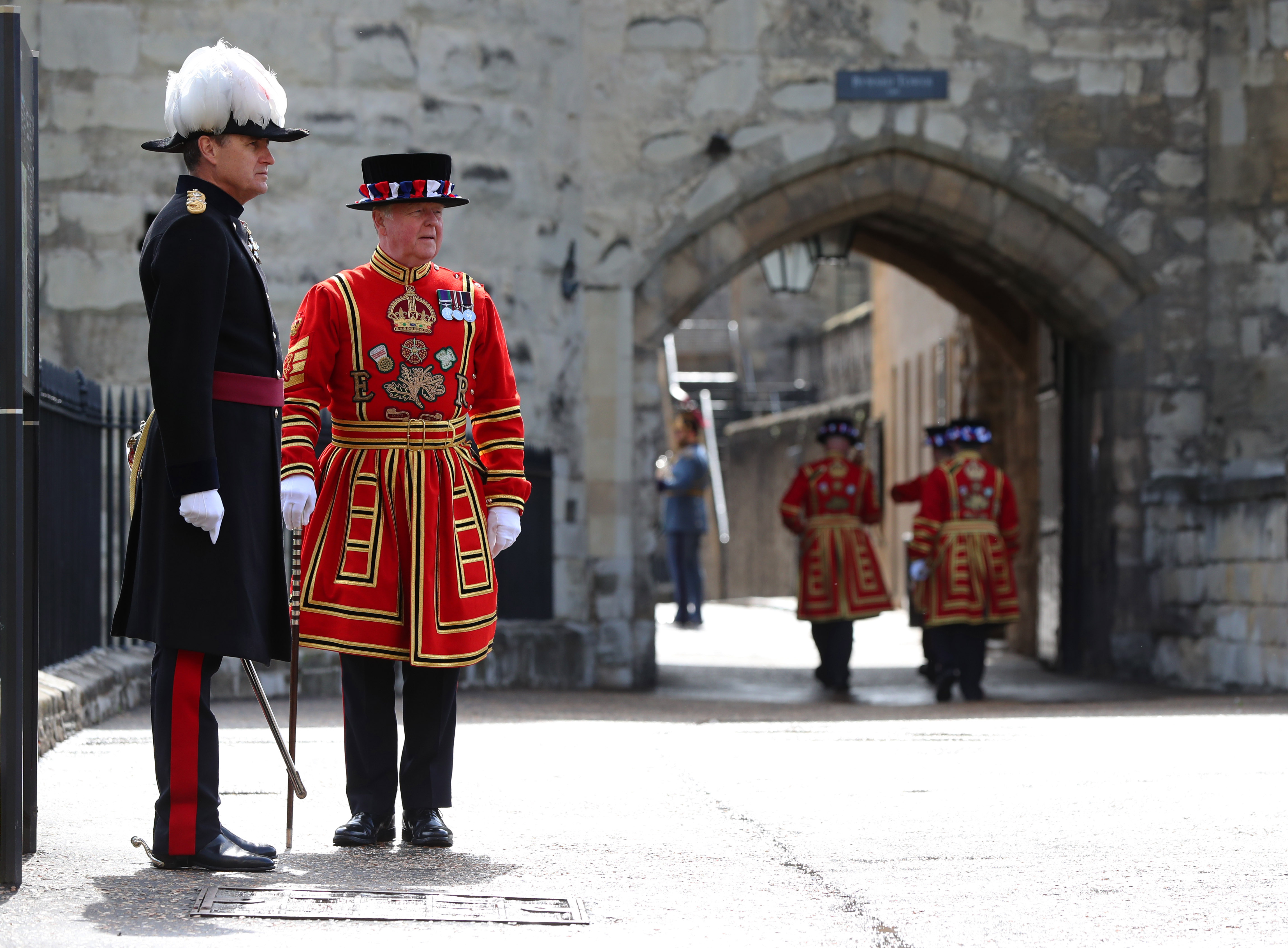 <p>Governor of the Tower of London Andrew Jackson (left) waits to greet visitors to the Tower of London, which is reopening amidst the easing of coronavirus restrictions after its longest closure since World War Two. Picture date: Wednesday May 19, 2021.</p>