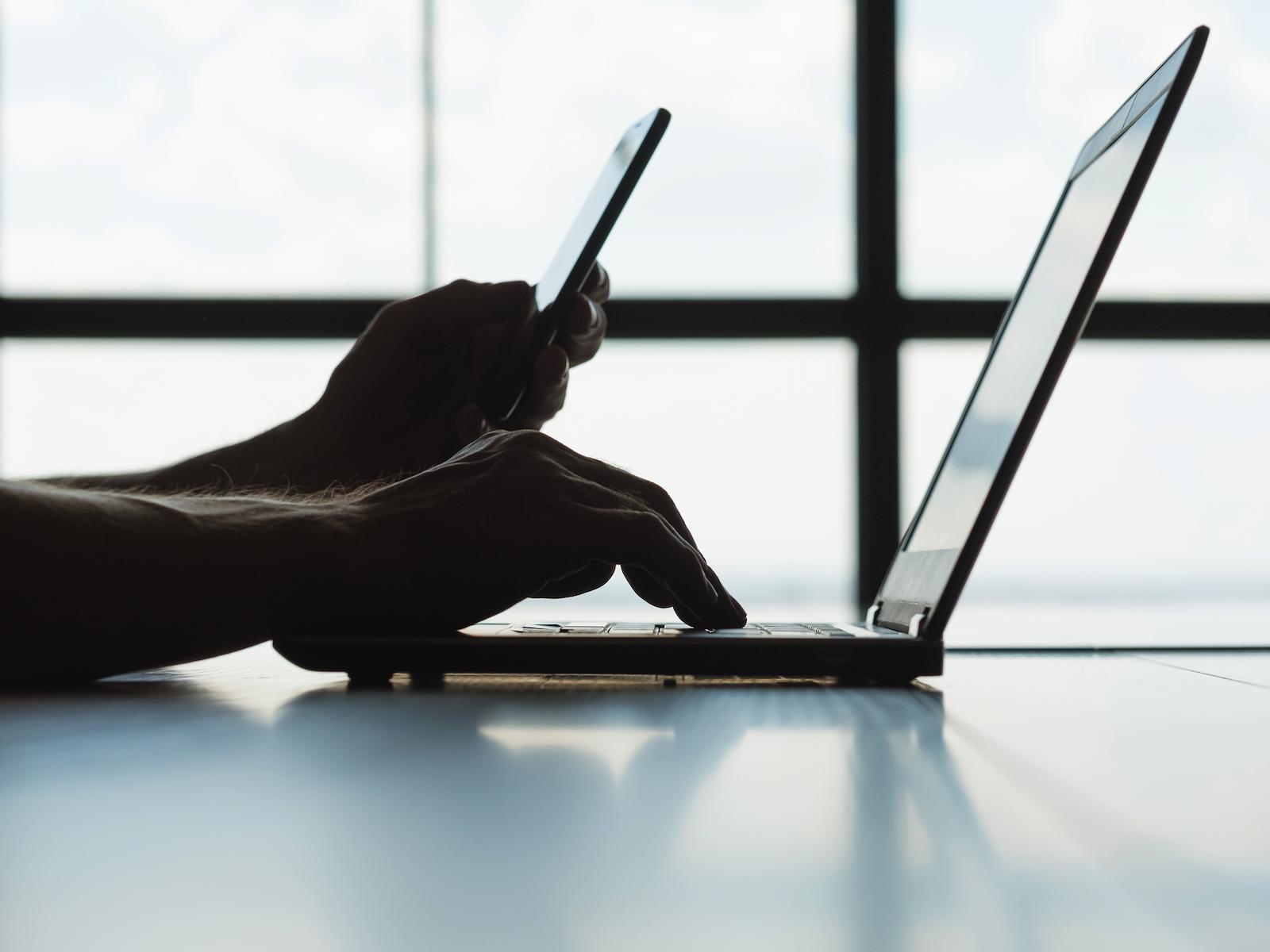 安全的在線支付。 兩要素授權。 男人手裡拿著手機和在筆記本電腦上輸入密碼消息。
