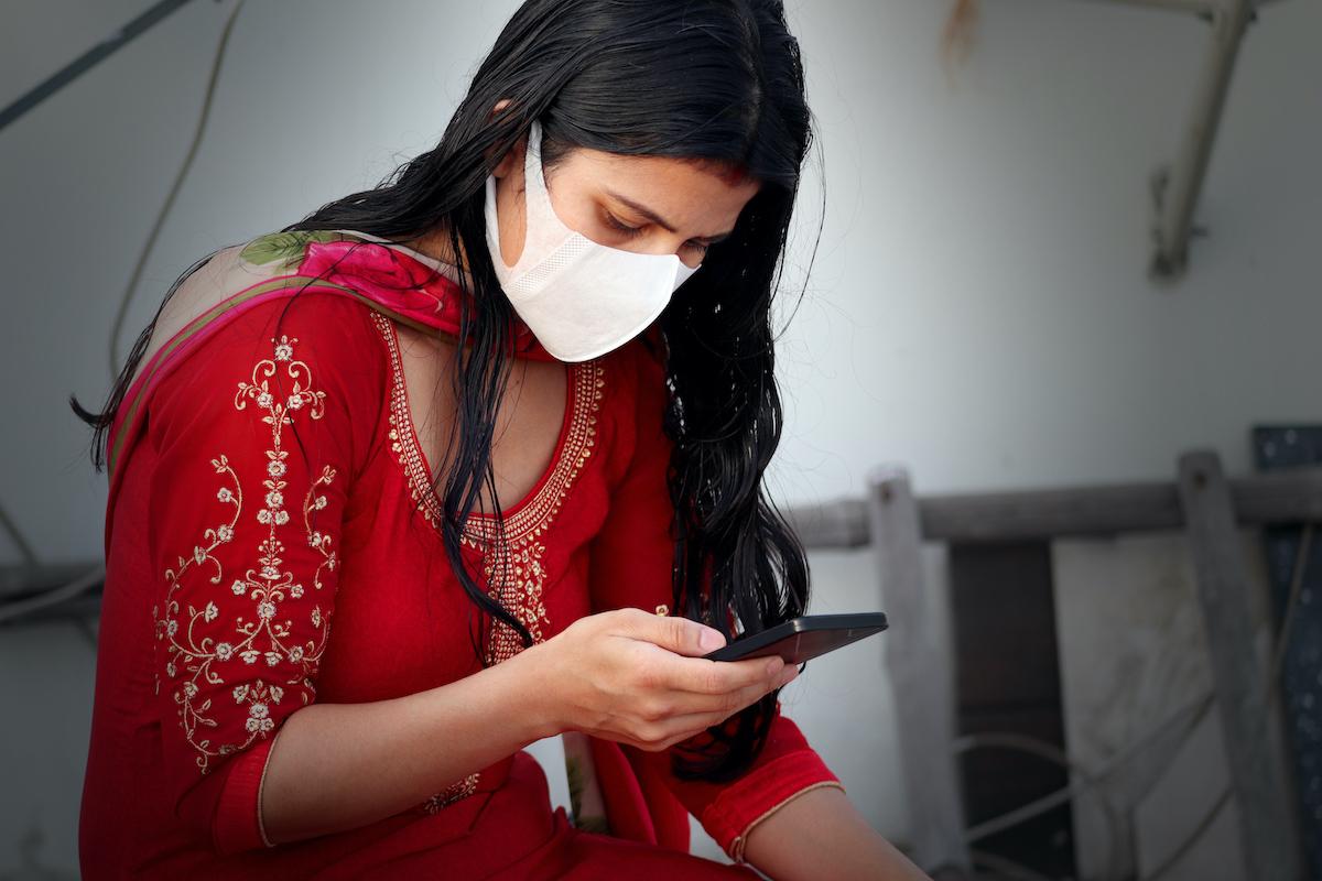 戴著污染面具的年輕印地安婦女反對冠狀病毒或COVID-19,並且她在家使用手機。
