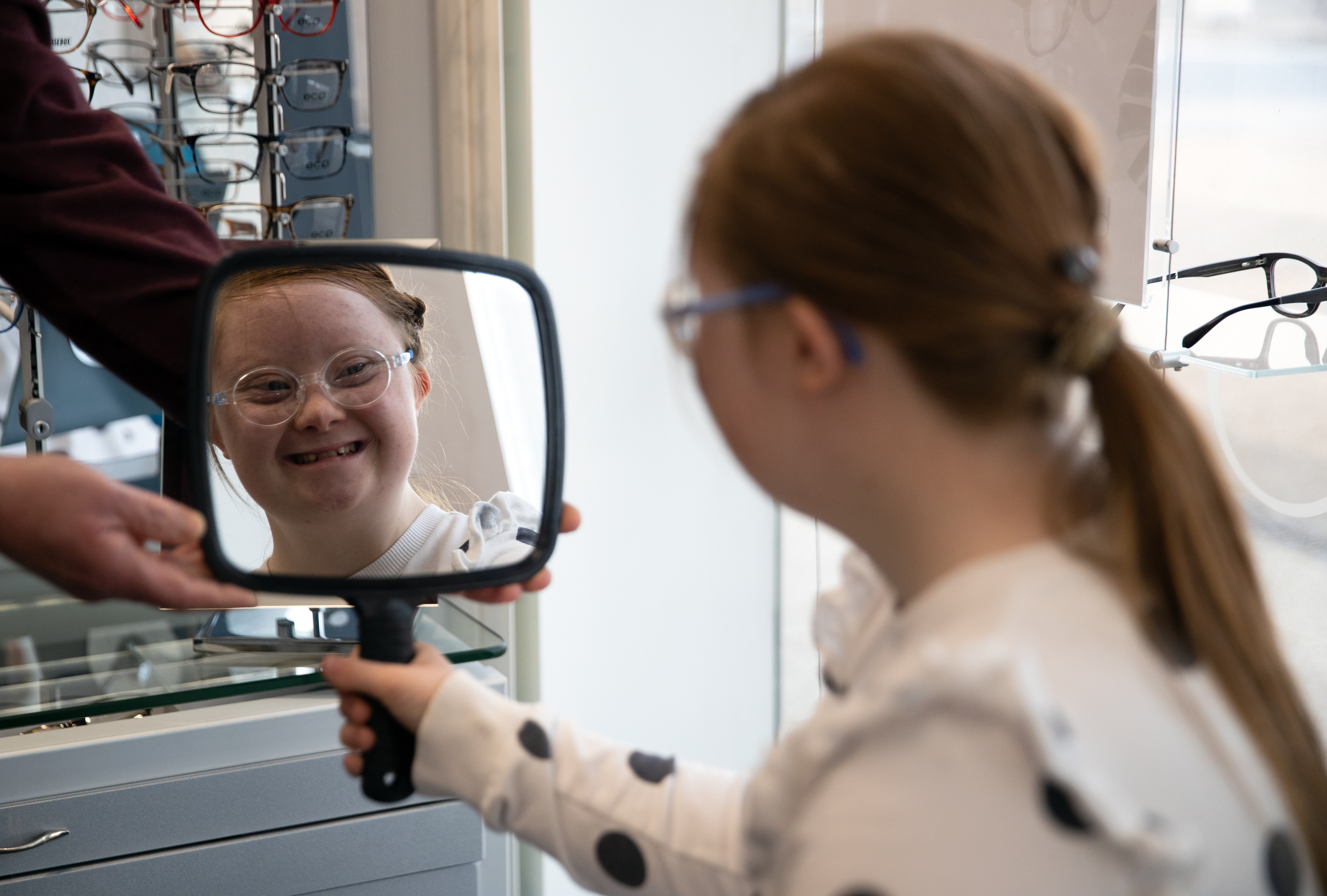<p>Rosie Johnson, 14, looks in a mirror as she tries on her new glasses at England's first Downs Syndrome eye clinic, at the University of Portsmouth in Hampshire, which has begun offering specialised treatment to people with Down Syndrome, saving them from having to travel to the UK's only other specialist centre in Wales. Picture date: Wednesday May 26, 2021.</p>
