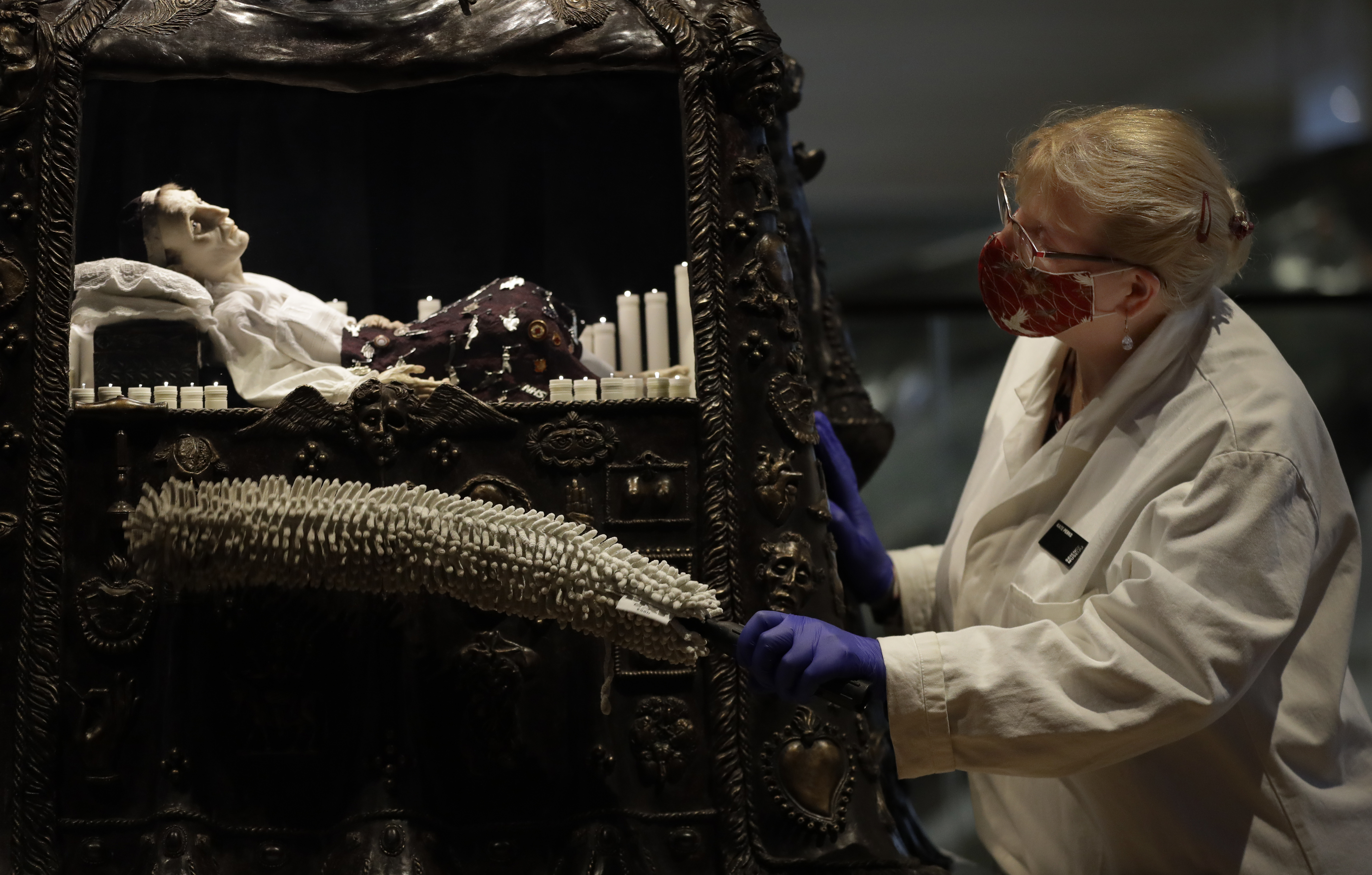 <p>Kate Perks, Senior Collections Care Conservator cleans a sculpture by Eleanor Crook called Santa Medicina, which combines medical and religious symbolism to help us reflect on the frailty of human life, displayed in Medicine: The Wellcome Galleries, at the Science Museum in London, Monday, May 17, 2021. The Science Museurm reopens to the public on Wednesday.  (AP Photo/Kirsty Wigglesworth)</p>