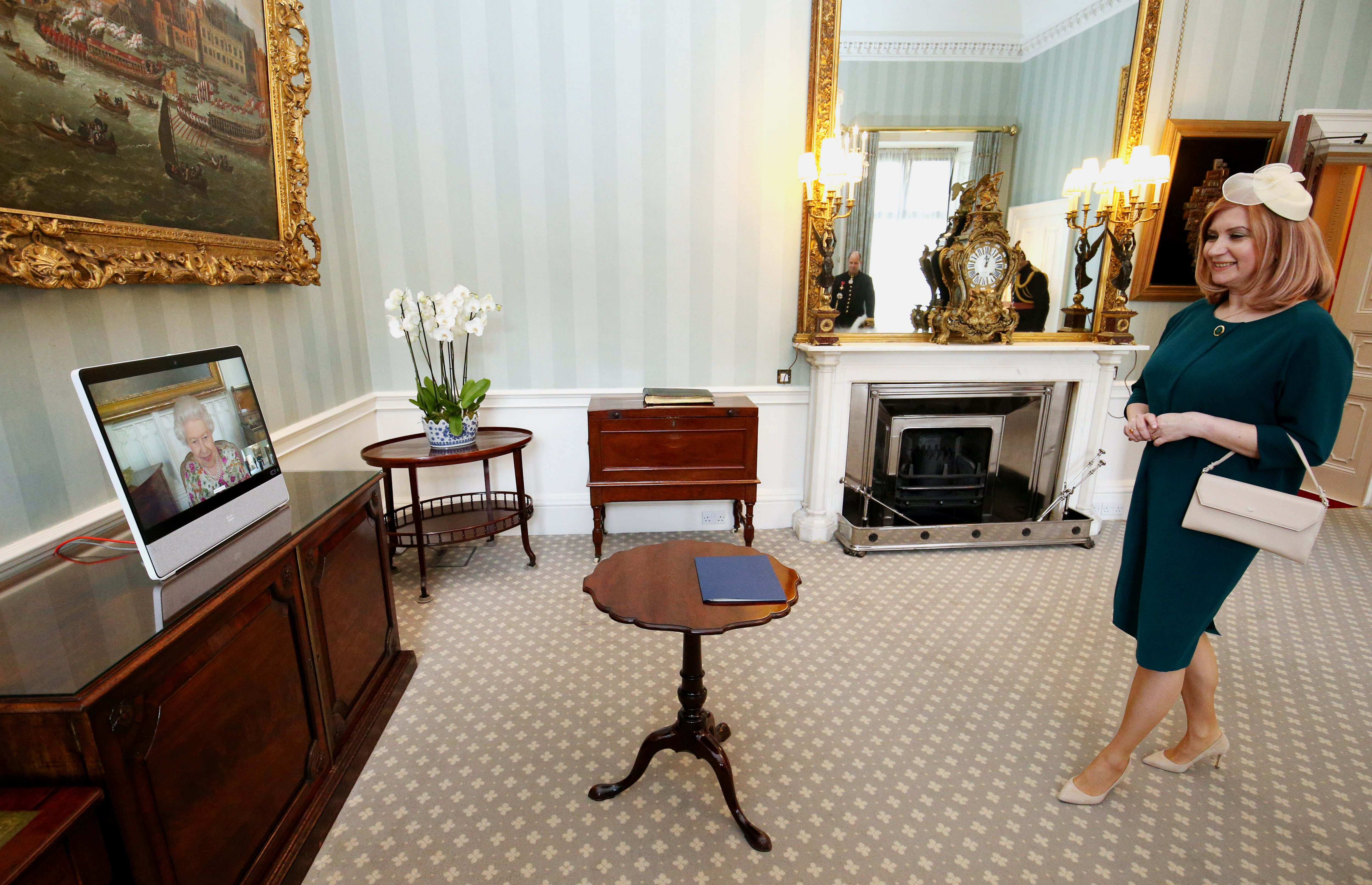 <p>Queen Elizabeth II appears on a screen by videolink from Windsor Castle, where she is in residence, during a virtual audience to receive the Ambassador of Romania Laura Popescu at Buckingham Palace, London. Picture date: Wednesday May 12, 2021.</p>