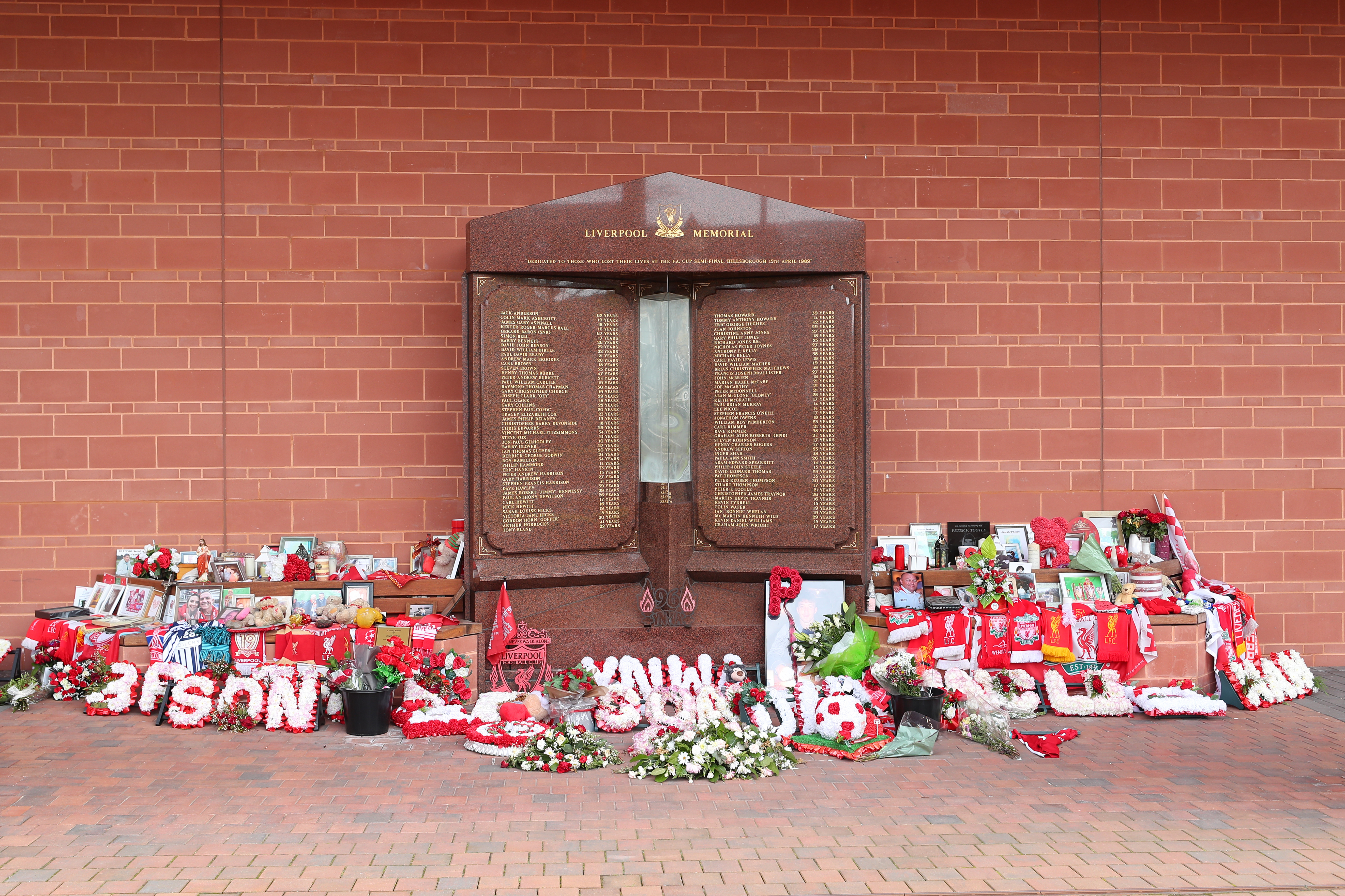 <p>Flowers and tributes left at the Hillsborough Memorial outside Anfield stadium, Liverpool, following the collapse of the Hillsborough trial. Picture date: Wednesday May 26, 2021. The judge at the Nightingale Court held at the Lowry in Salford, Greater Manchester, has ruled there is no case to answer in the trial of two retired police officers, Alan Foster and Donald Denton, and retired solicitor Peter Metcalf, who were all accused of perverting the course of justice following the Hillsborough disaster on April 15, 1989.</p>