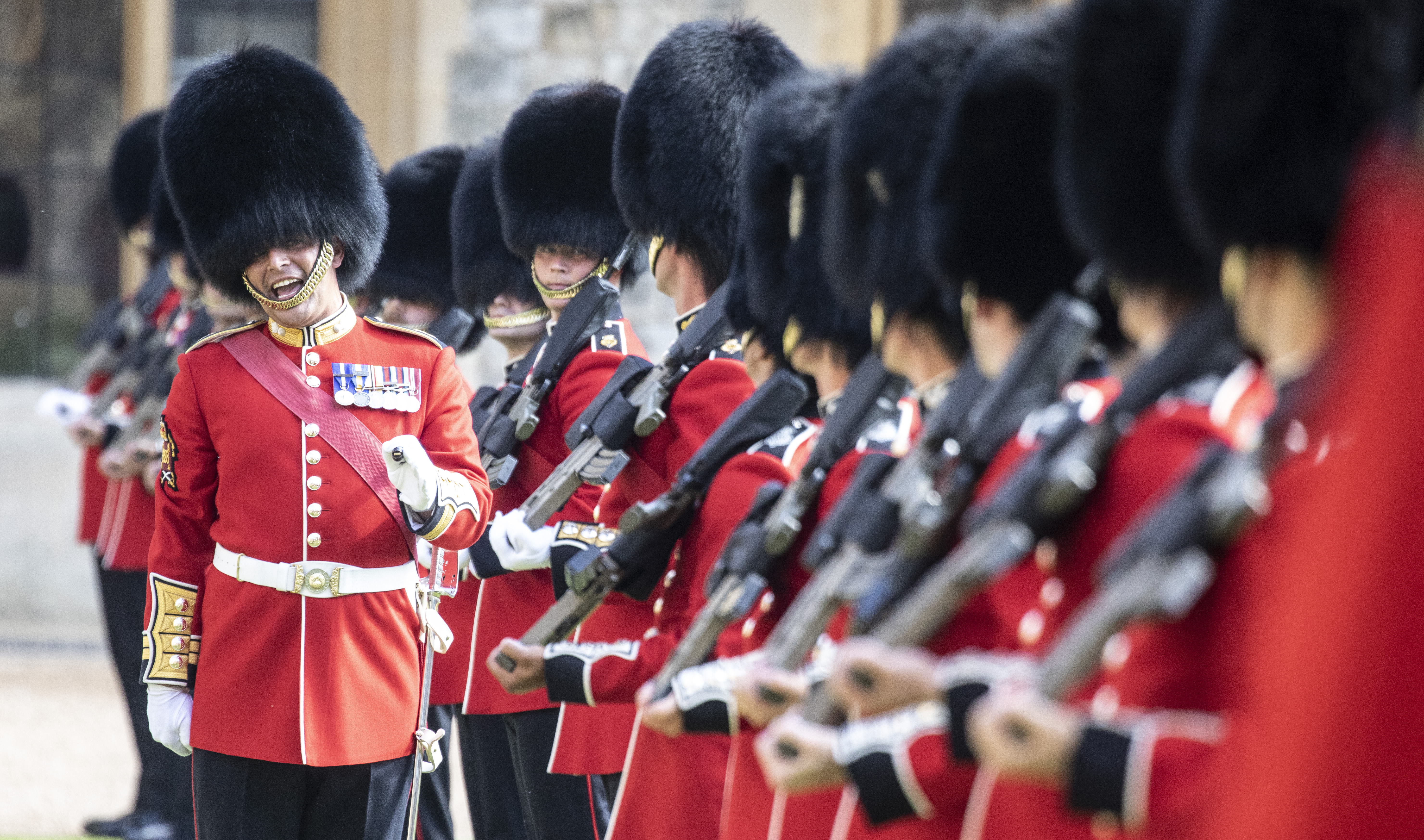 <p>WINDSOR, ENGLAND - JUNE 13: A warrant officer shouts instructions as he inspects the line of a Guard of Honour formed of The Queen's Company First Battalion Grenadier Guards at Windsor castle on June 11, 2021 in Windsor, England.  Queen Elizabeth II hosts US President, Joe Biden and First Lady, Dr Jill Biden, at Windsor Castle. The President arrived from Cornwall where he attended the G7 Leader's Summit and will travel on to Brussels for a meeting of NATO Allies and later in the week he will meet President of Russia, Vladimir Putin. (Photo by Richard Pohle-WPA Pool/Getty Images)</p>