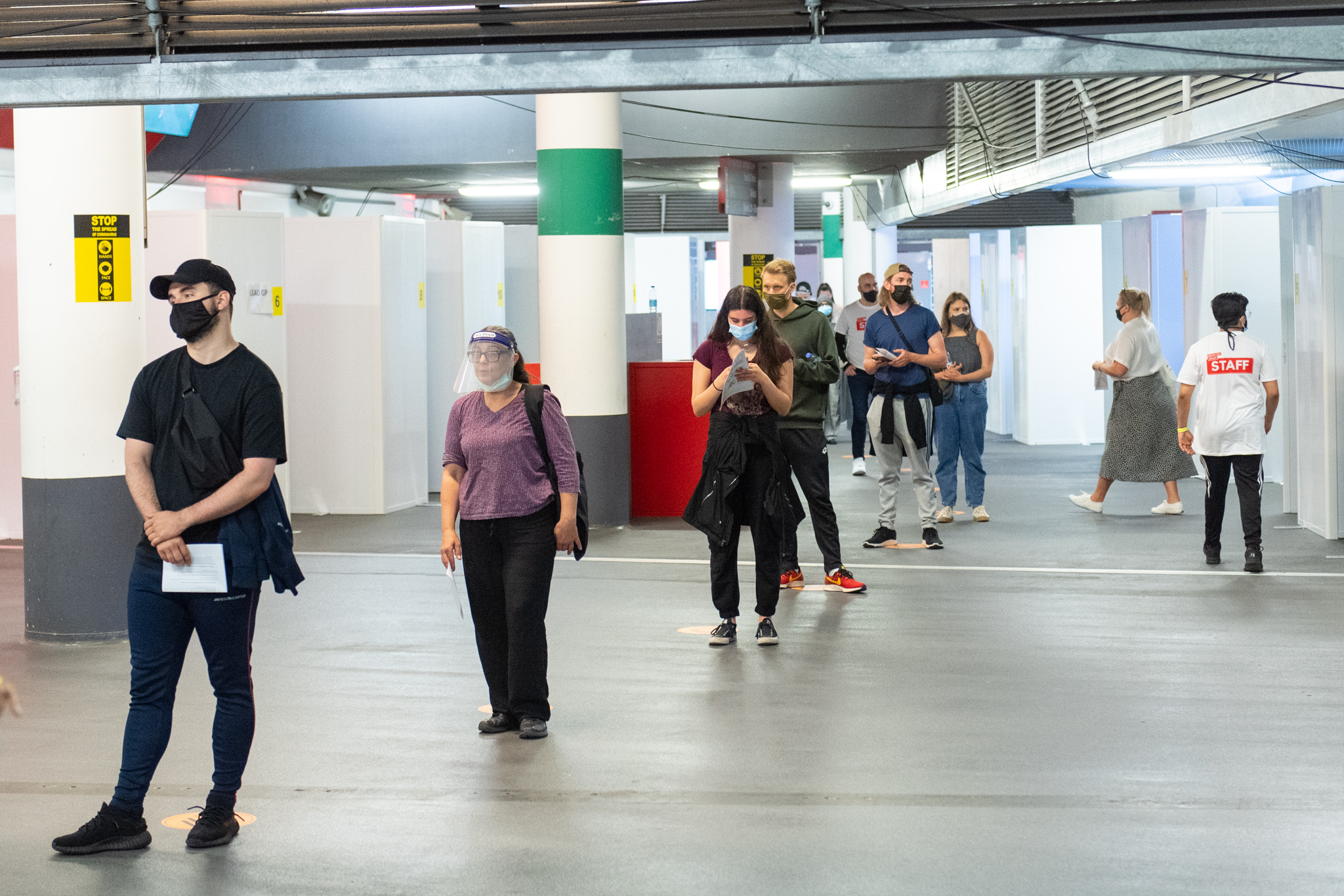 <p>People queue inside a mass coronavirus vaccination centre at Arsenal's Emirates Stadium, in north London, run by Islington Council and Islington GP Federation in partnership with Arsenal Football Club. Picture date: Friday June 25, 2021.</p>