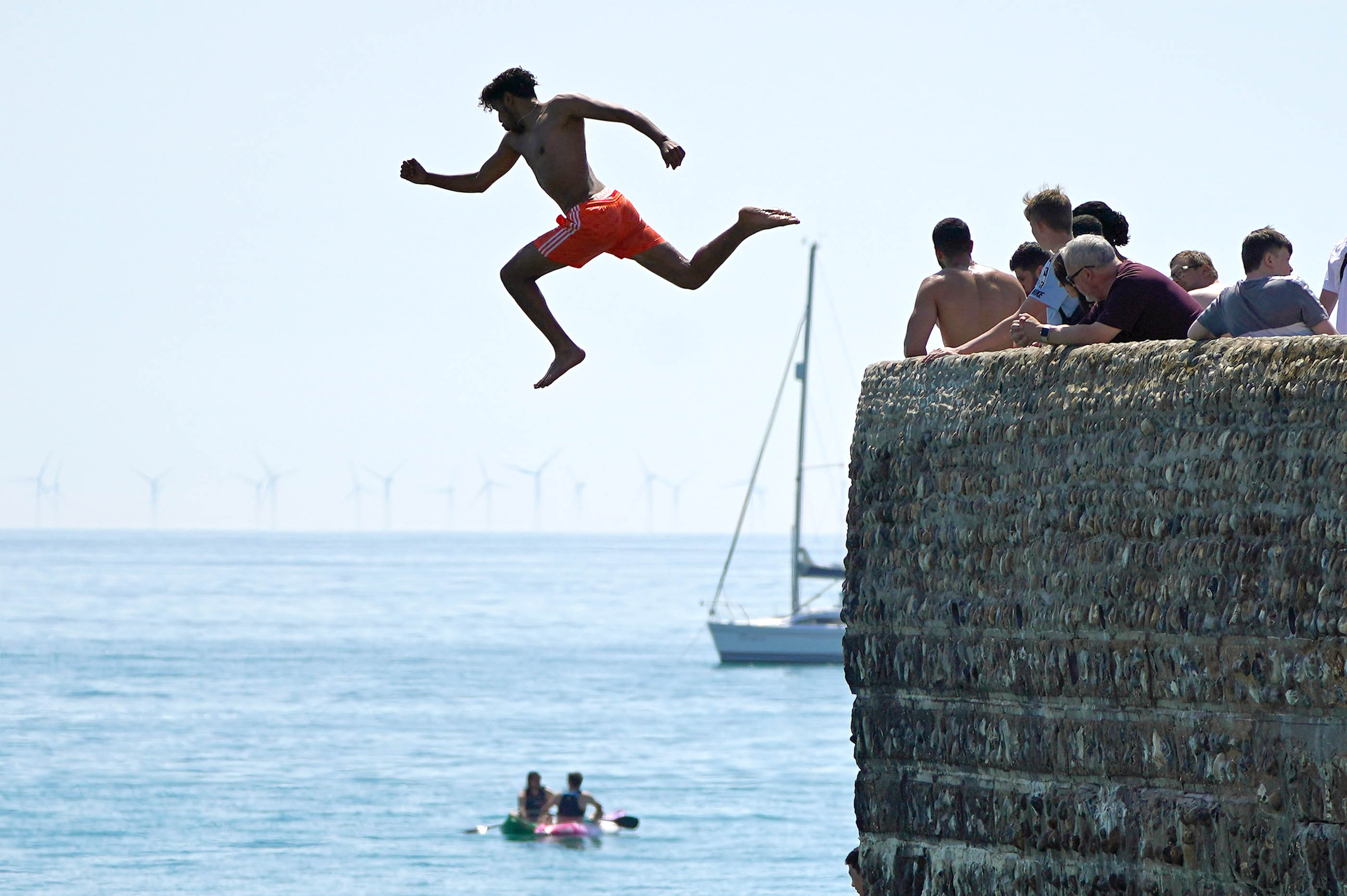 <p>A man jumps into the sea whilst people enjoy the sunshine on Brighton beach. Wednesday could be the hottest day of the year so far as parts of the UK are set to bask in 30-degree heat. Picture date: Wednesday June 16, 2021.</p>