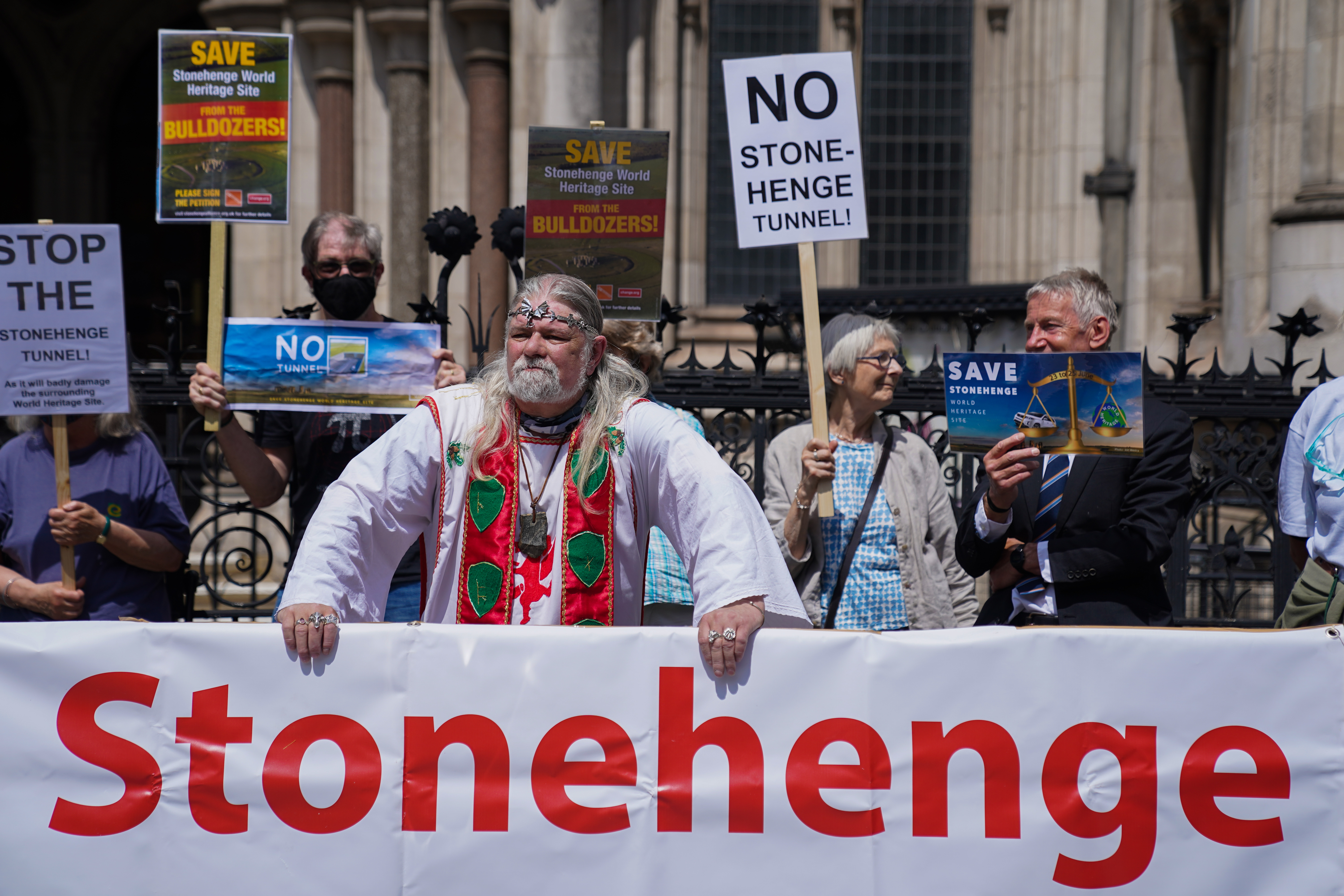 <p>Campaigners outside the High Court, central London, where they are fighting to block a controversial road project which includes a tunnel near Stonehenge. Picture date: Wednesday June 23, 2021.</p>