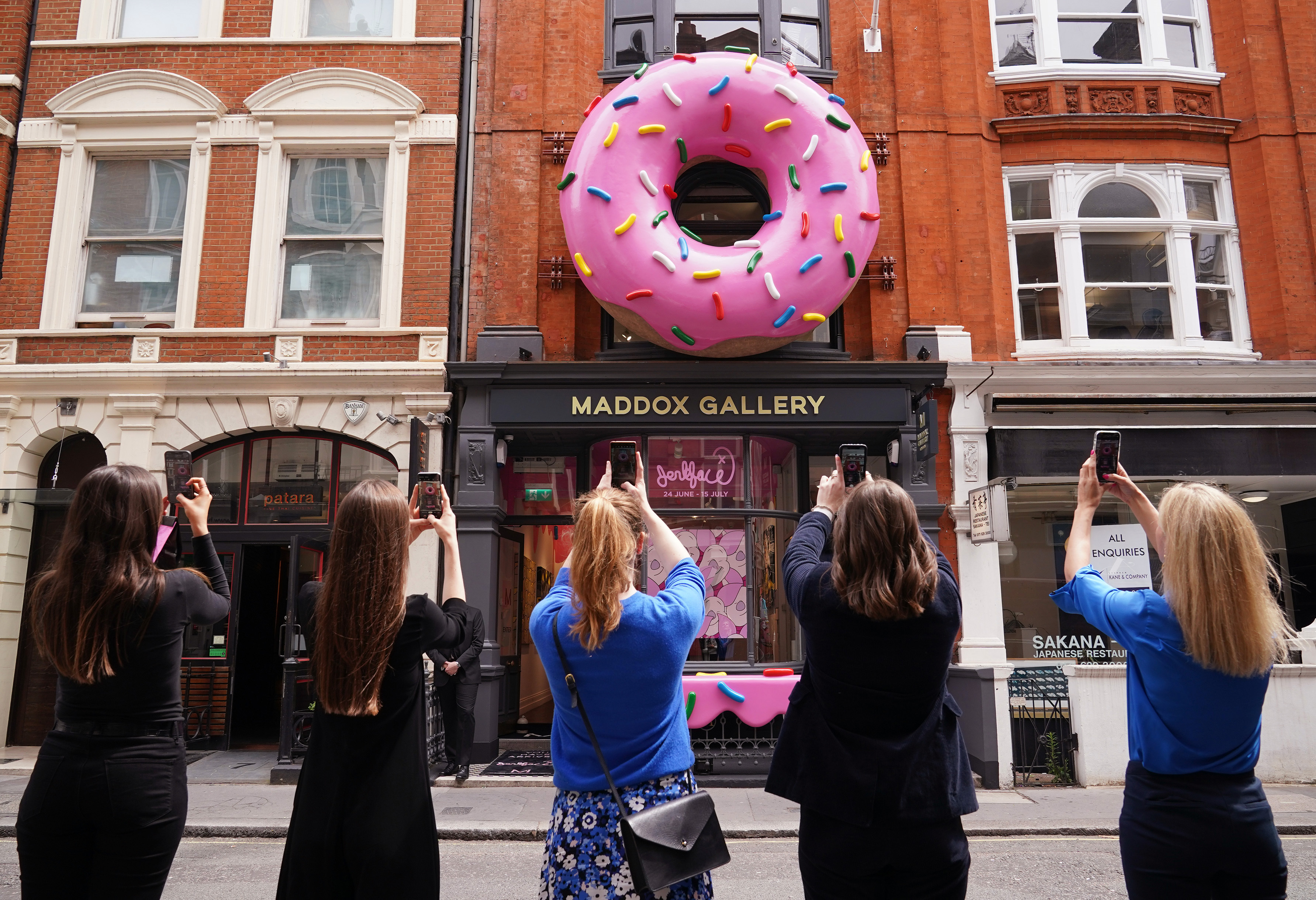 <p>A group of women take photos of a giant donut installation outside the Maddox Gallery in Mayfair, London, to celebrate a new exhibition entitled Villainy, a body of work by an anonymous street artist from New York who operates under the alias, 'Jerkface'. Picture date: Thursday June 24, 2021.</p>