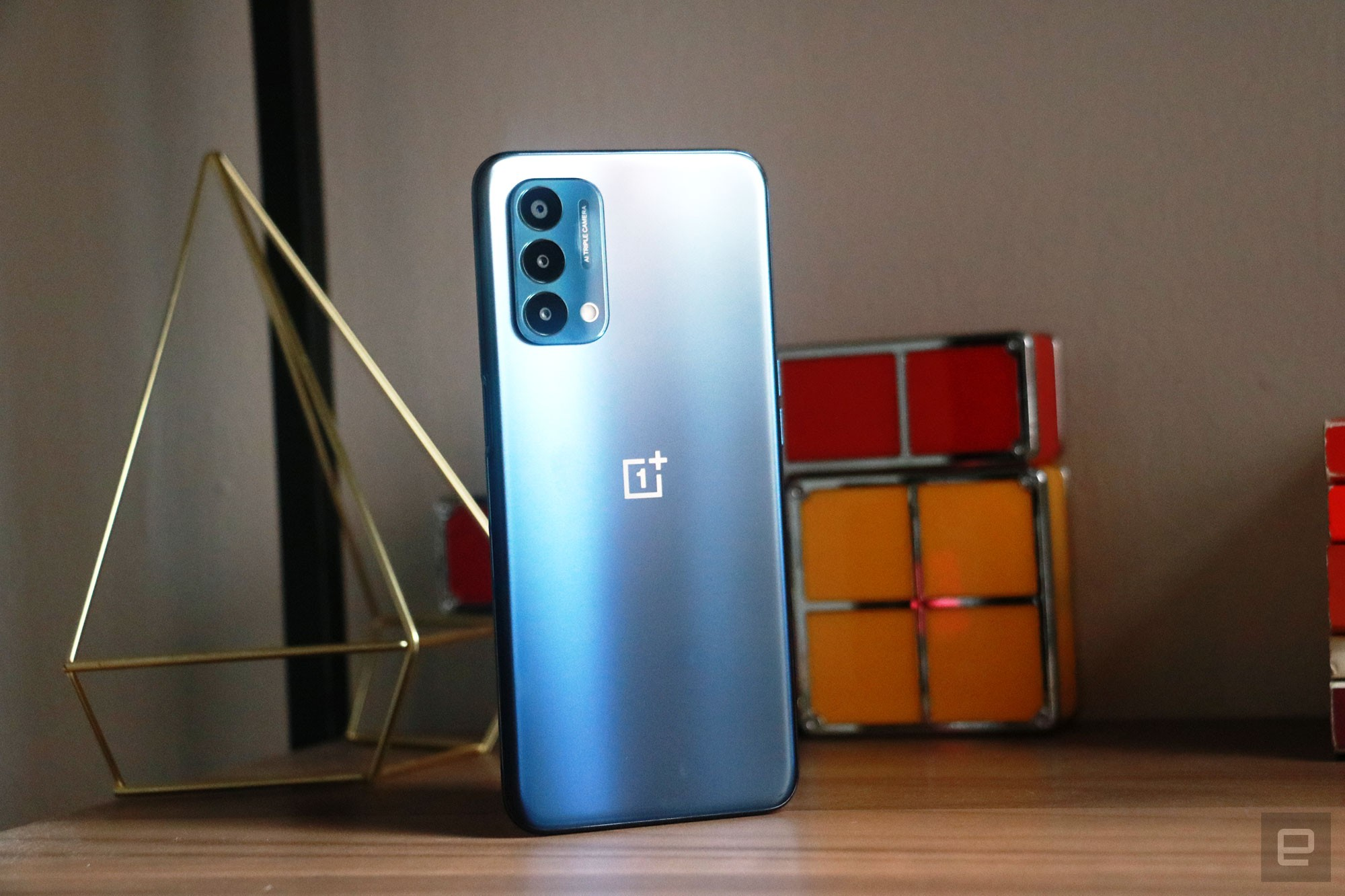 <p>OnePlus Nord N200 5G. Off angle view of the phone sitting on a shelf with ornaments in the background with its rear facing outwards.</p>
