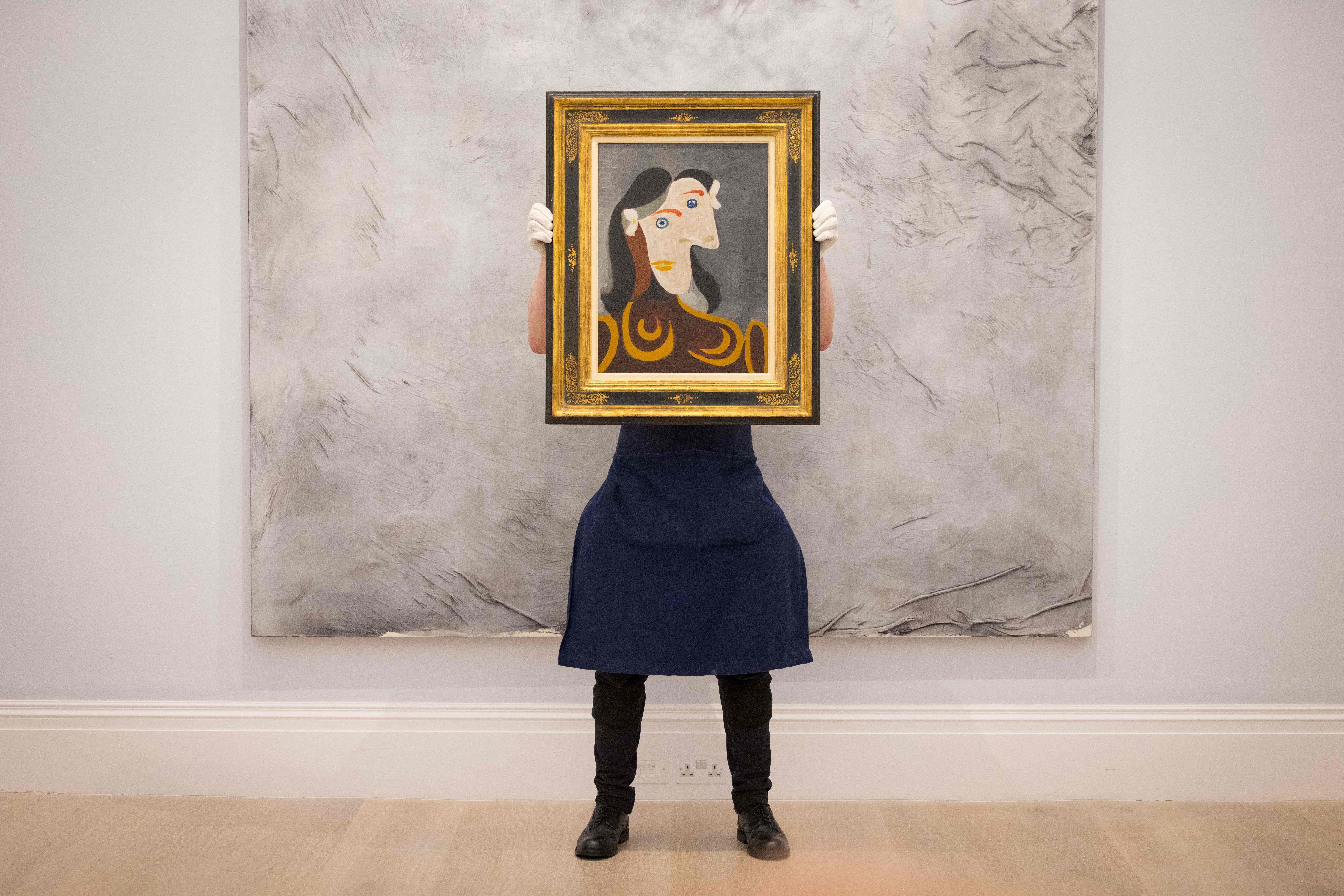 <p>TOPSHOT - A gallery worker poses with an artwork entitled Buste de femme à la robe brune by Spanish painter Pablo Picasso during a photocall at the preview of Sotheby's Major Summer Auctions at Sothebys auction house in central London on June 22, 2021. - - RESTRICTED TO EDITORIAL USE - MANDATORY MENTION OF THE ARTIST UPON PUBLICATION - TO ILLUSTRATE THE EVENT AS SPECIFIED IN THE CAPTION (Photo by Tolga Akmen / AFP) / RESTRICTED TO EDITORIAL USE - MANDATORY MENTION OF THE ARTIST UPON PUBLICATION - TO ILLUSTRATE THE EVENT AS SPECIFIED IN THE CAPTION / RESTRICTED TO EDITORIAL USE - MANDATORY MENTION OF THE ARTIST UPON PUBLICATION - TO ILLUSTRATE THE EVENT AS SPECIFIED IN THE CAPTION (Photo by TOLGA AKMEN/AFP via Getty Images)</p>