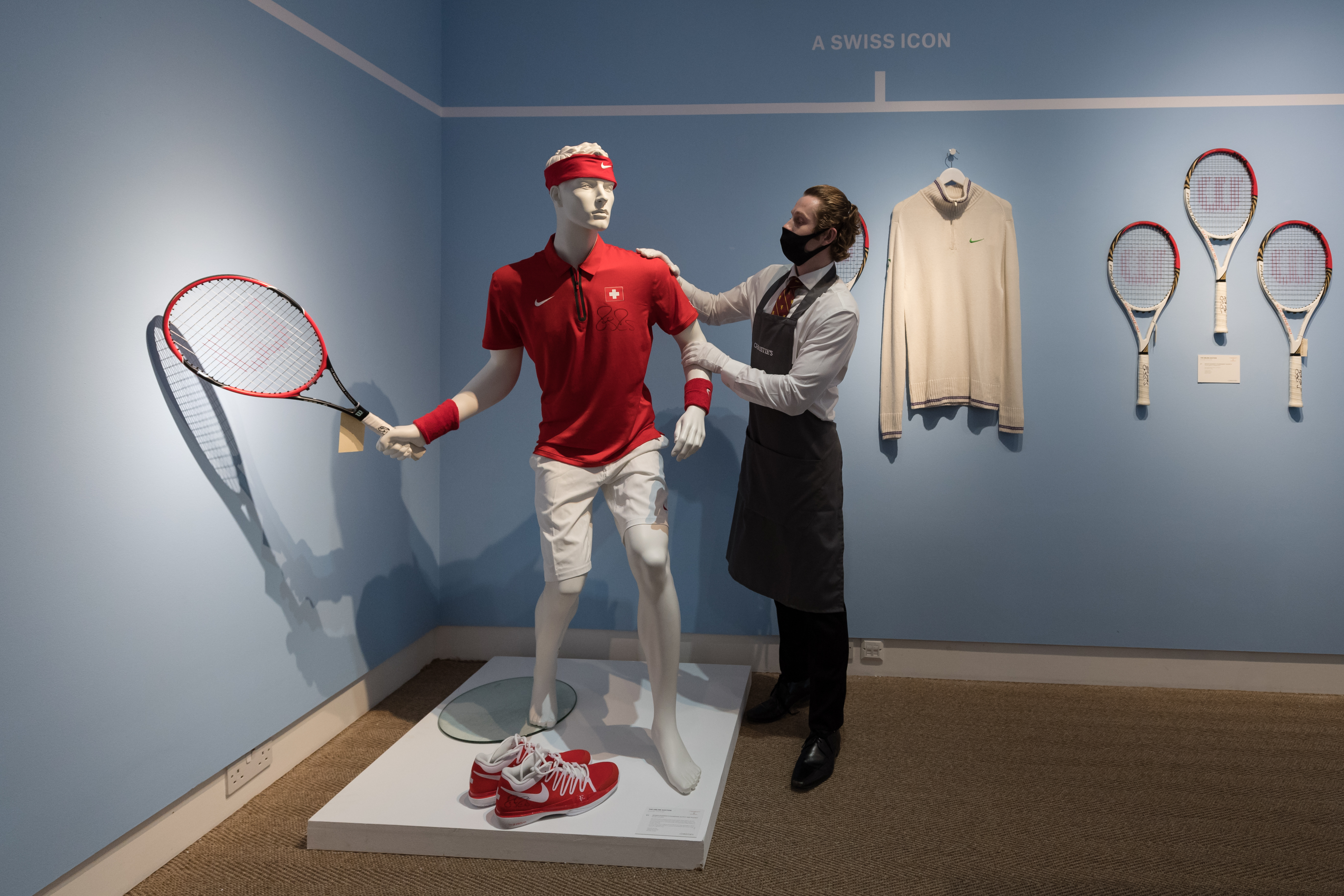 <p>LONDON, UNITED KINGDOM - JUNE 21: A staff member stands next to Roger Federer's signed champion outfit and racket from 2014 Davis Cup (est. £20,000-30,000) during a photo call for 'The Roger Federer Collection: Sold to Benefit The RF Foundation' Evening and Online Sale at Christie's auction house in London, United Kingdom on June 21, 2021. The collection celebrates Federerâs historic achievements, with sporting memorabilia from his Grand Slam victories offered for auction in London on 23 June together with an online sale (23 June â 13 &amp; 14 July), which chronicles his incredible career from the early 2000s right through to 2021. (Photo by Wiktor Szymanowicz/Anadolu Agency via Getty Images)</p>
