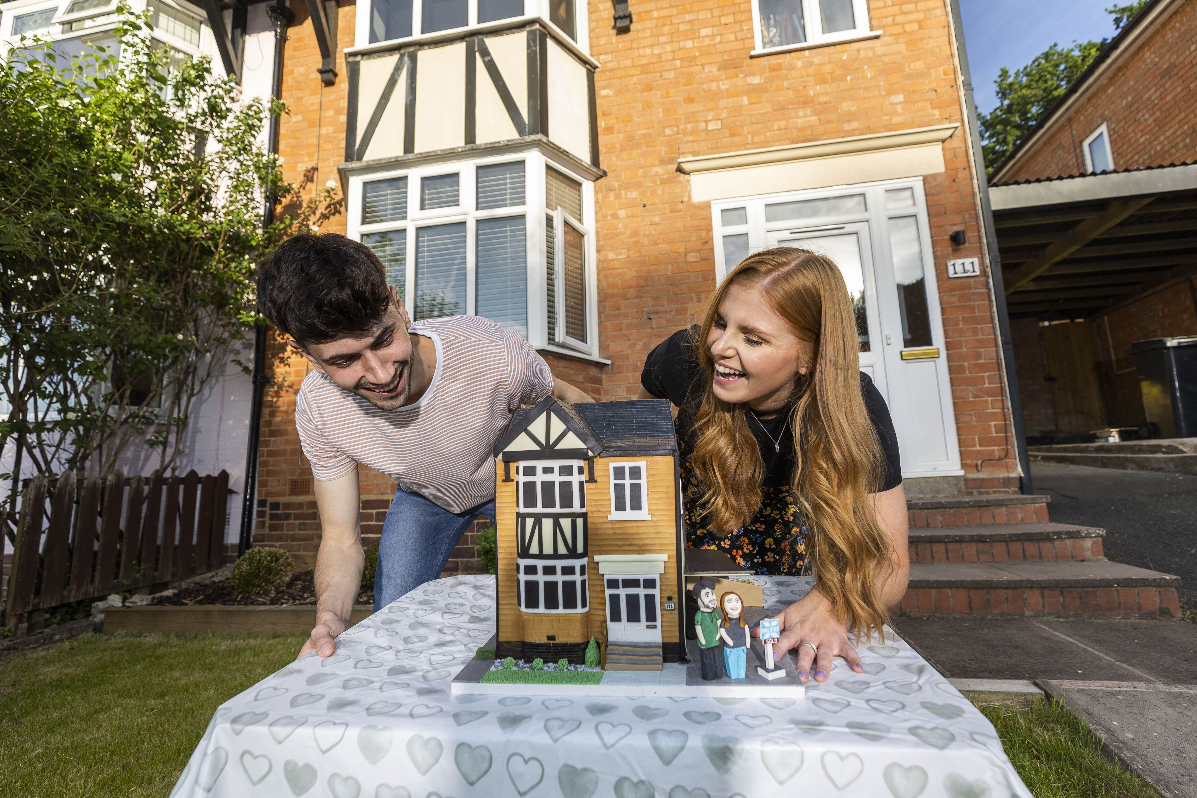 <p>EDITORIAL USE ONLY First-time buyers, George Isaacs and Lauren Turner are presented with a �First-Home� celebration cake outside their new home in Redditch, which has been created by Ben Cullen, The Bake King, to help new homeowners mark their home-buying milestone, as research from Halifax finds that a fifth of Brits would spend less on a wedding since the pandemic and more would prioritise buying a first home. Despite couples seeing a house purchase as a bigger relationship commitment than a wedding, just two-fifths of young people would consider celebrating the achievement with loved ones. Issue date: Thursday June 17, 2021.</p>