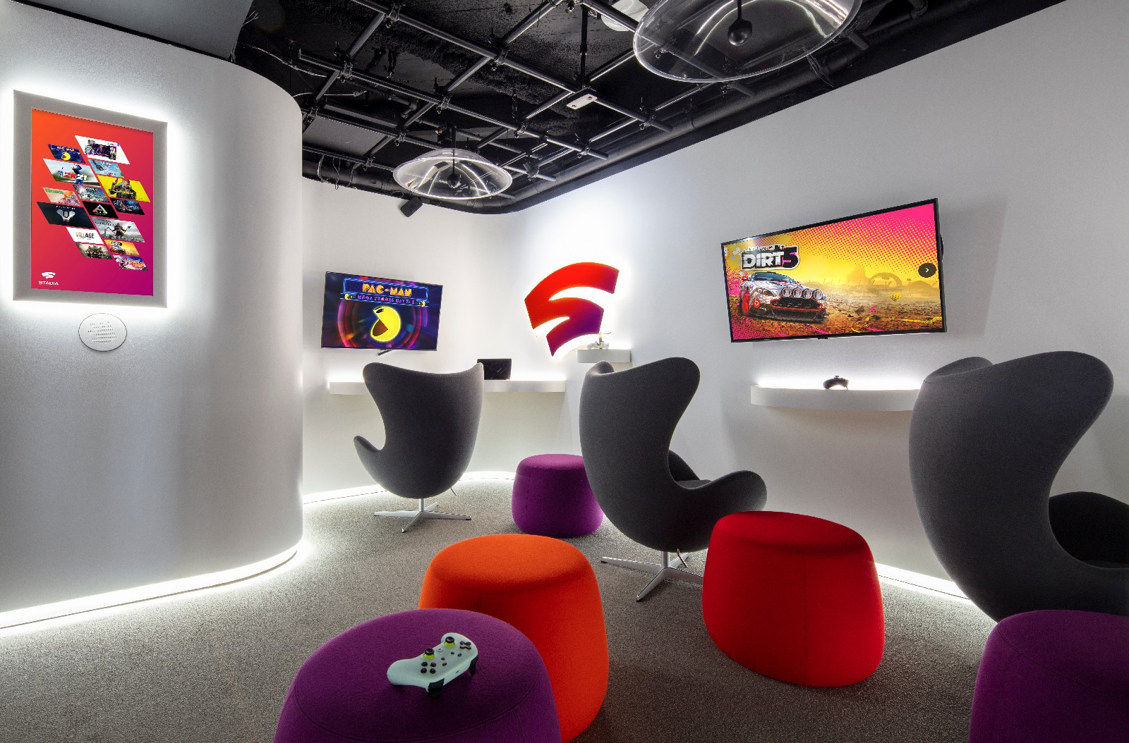 <p>Google Store Chelsea. A Stadia-themed Sandbox with wall-mounted screens, three chairs, four stools in matching purple and orange colors and a couple of controllers lying on small ledges.</p>