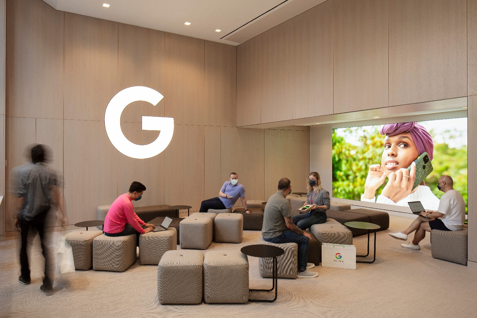 <p>Google Store Chelsea. A workshop area with several ottomans and small tables. The Google logo (letter G only) on the wall is lit in a soft white. Six people ar eseated at various spots in the room.</p>