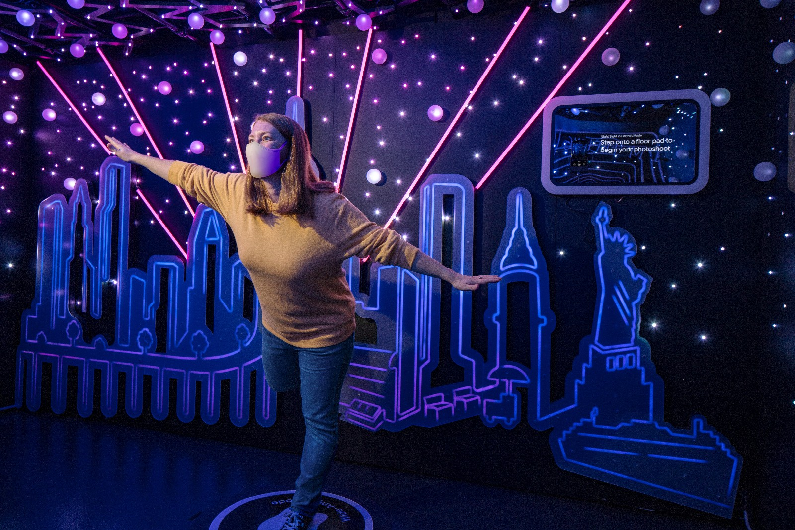 <p>Google Store Chelsea. A Night Sight-themed Sandbox with a person wearing a face mask posing in the middle. The background features a cut-out art rendering of the New York City skyline with rays of pink light emanating from it and the Statue of Liberty on the right. A display is on the wall above this.&nbsp;</p>