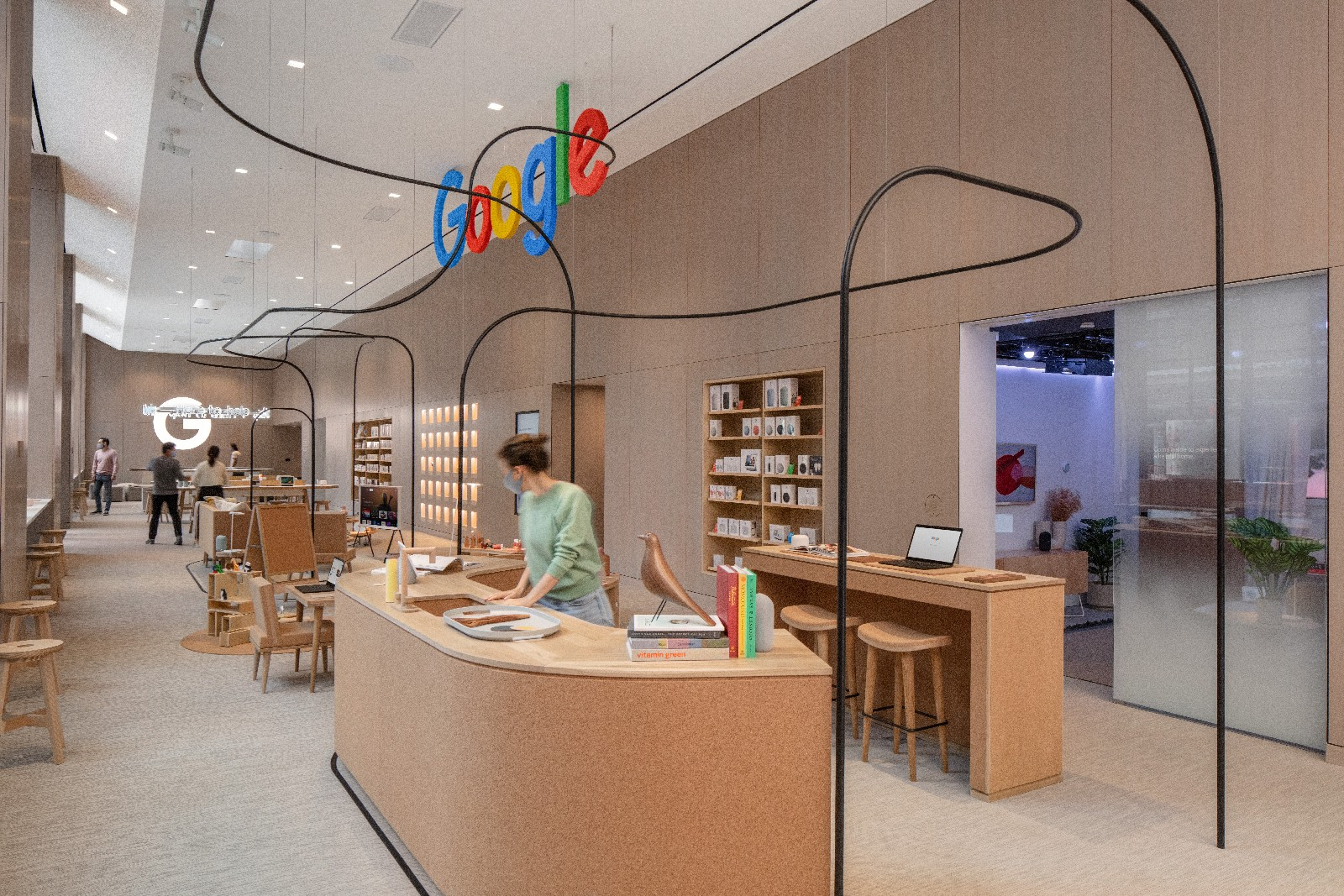 <p>Google Store Chelsea. Interior, featuring several curving light wood desks and stools.</p>