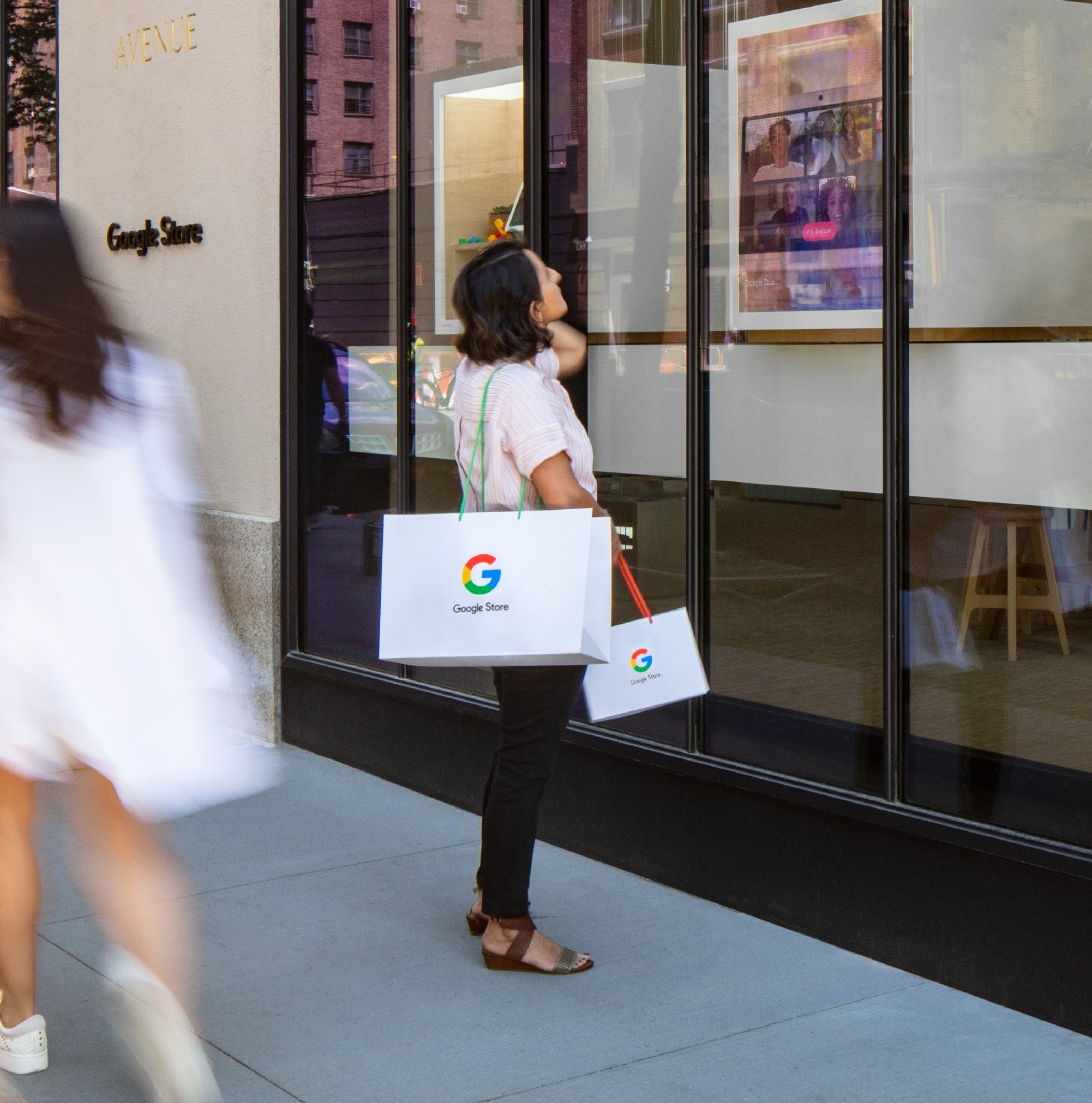 <p>Google Store Chelsea. A person outside the store carrying two Google-branded shopping bags looks at one of the displays facing the street.</p>