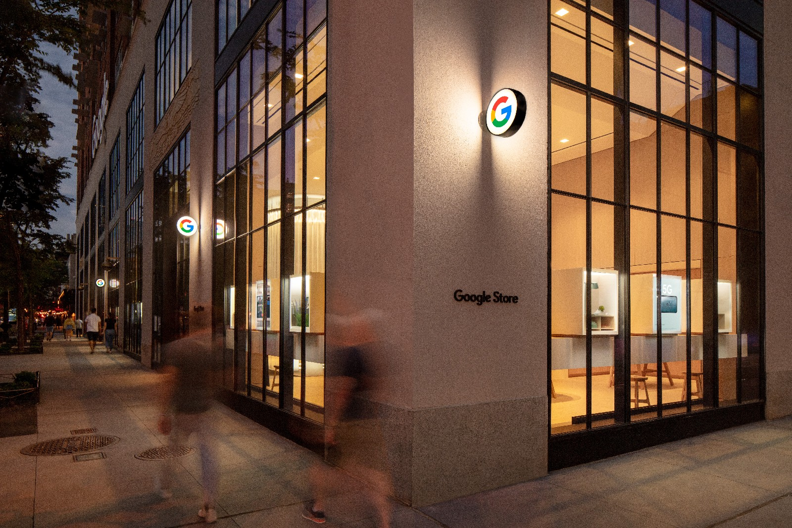<p>Google Store Chelsea. Exterior facade at night with blurs of two people walking by.</p>