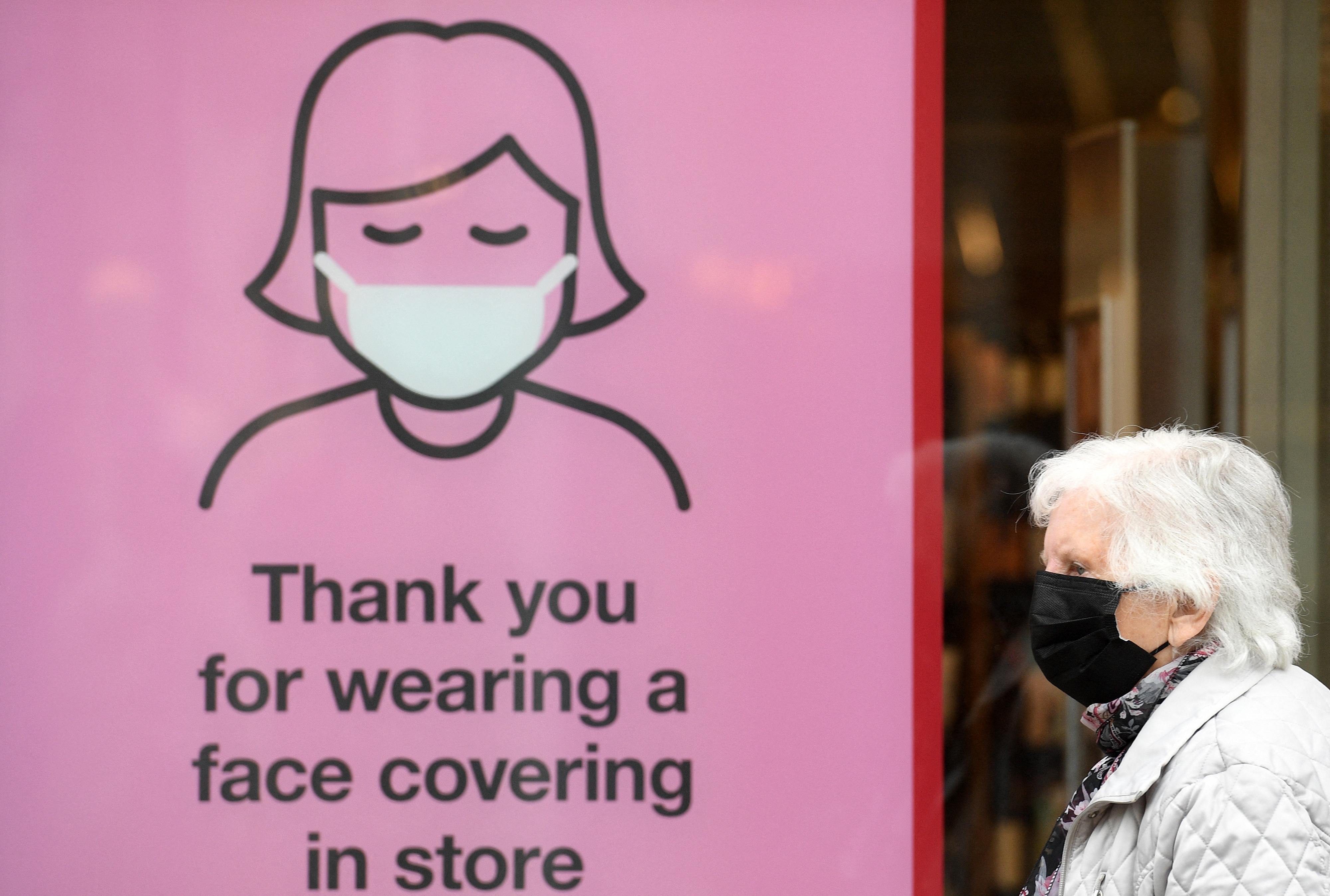 <p>A members of the public wearing a face mask passes a sign asking shoppers to face coverings inside the store, in Cumbria, north west England on June 21, 2021, where surge testing has been deployed following an outbreak of a coronavirus variant of concern. (Photo by Oli SCARFF / AFP) (Photo by OLI SCARFF/AFP via Getty Images)</p>