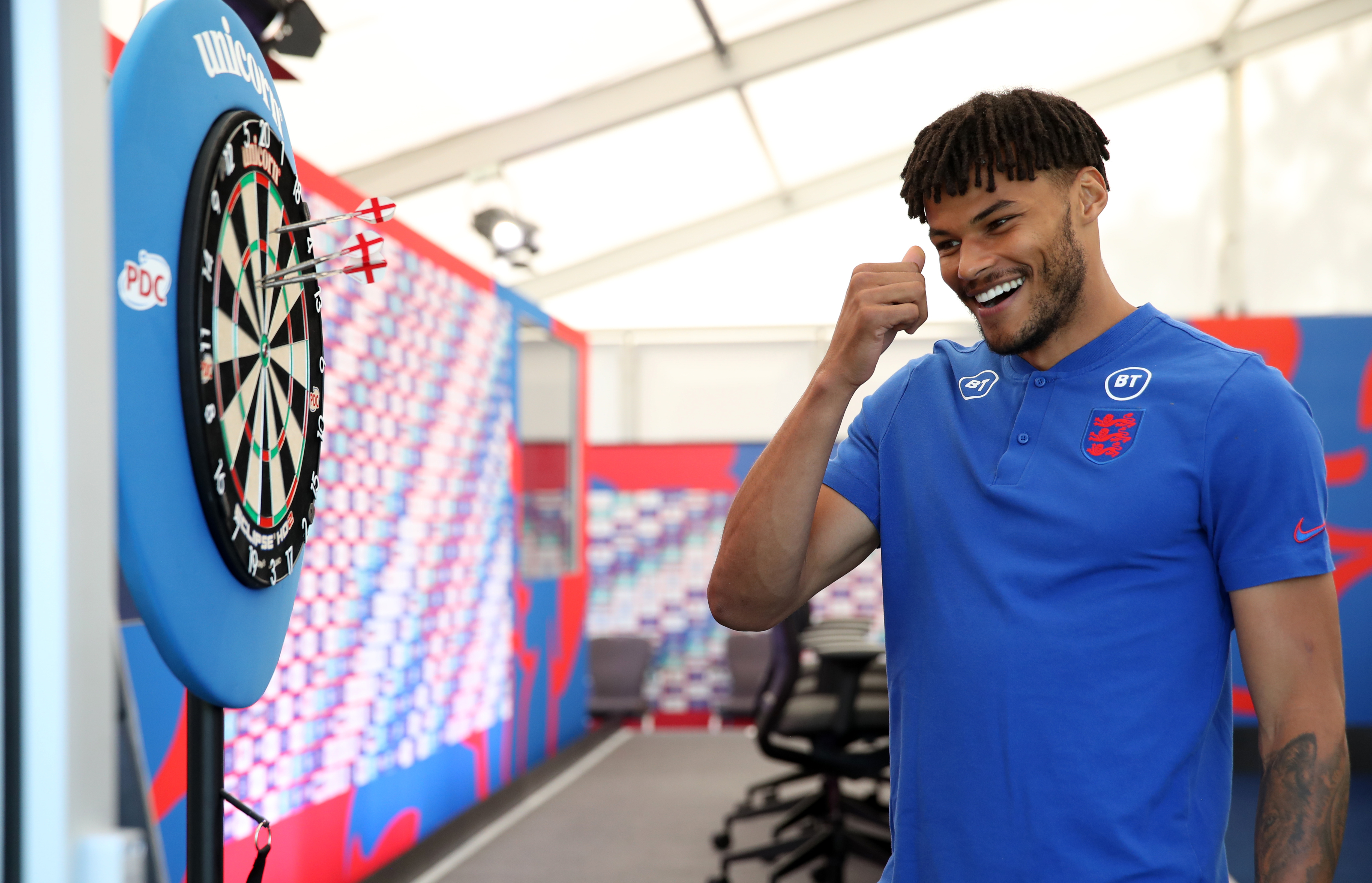 <p>England's Tyrone Mings plays darts with media following the press conference at St George's Park, Burton upon Trent. Picture date: Tuesday June 15, 2021.</p>