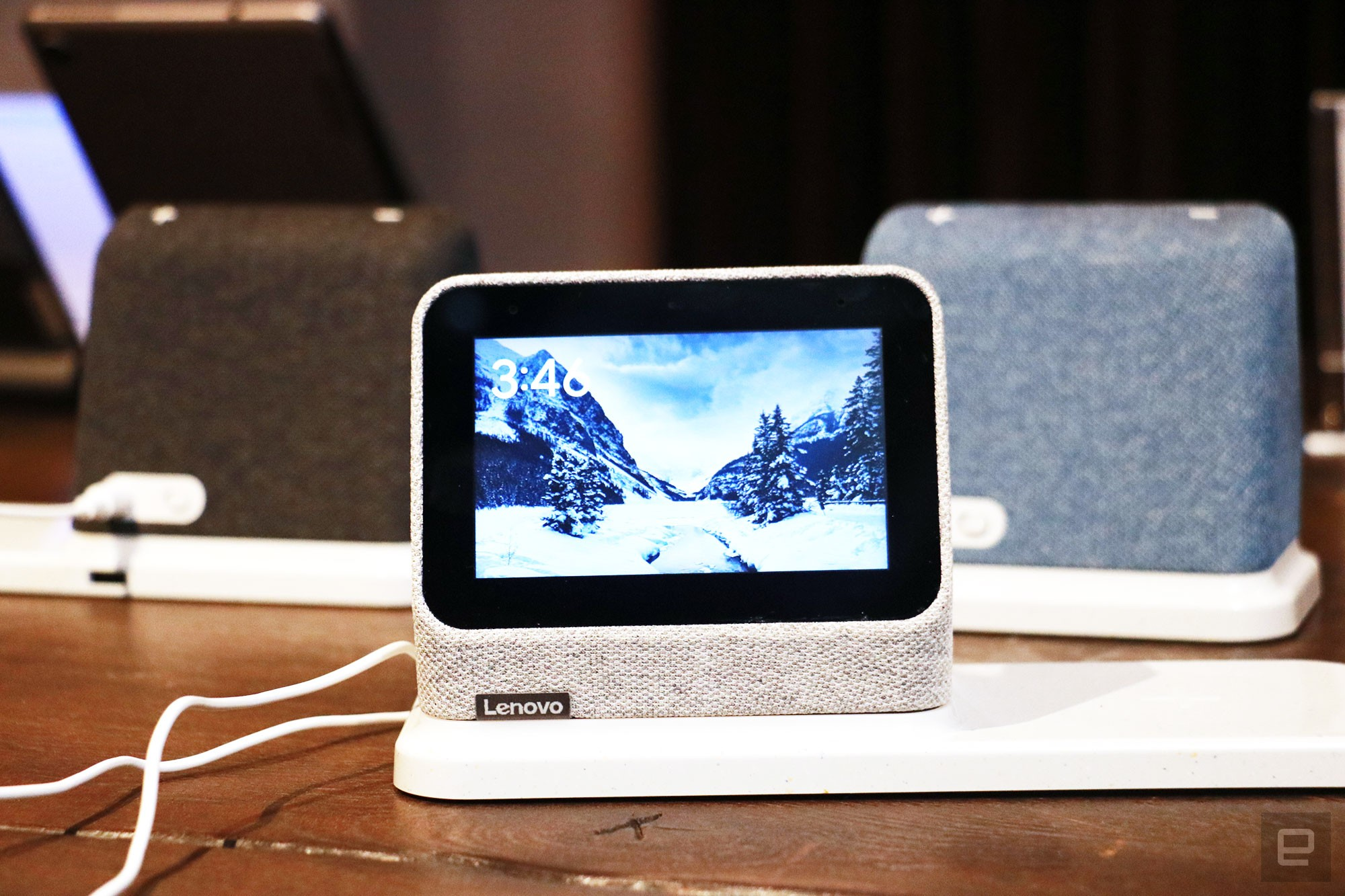 <p>A gray Lenovo Smart Clock 2 on a wireless charging dock with its screen facing the camera. In the background are a black and a blue Smart Clock 2 on the left and right respectively.</p>