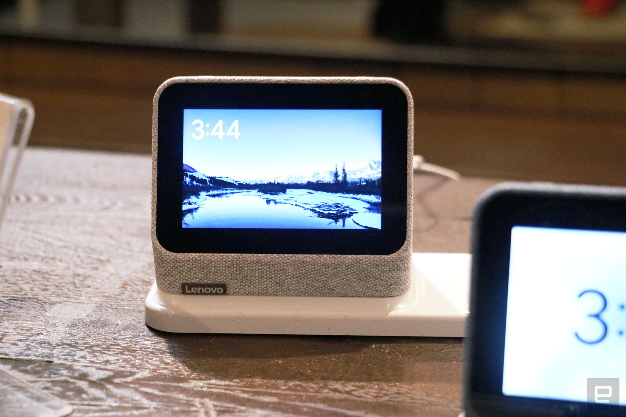 <p>A gray Lenovo Smart Clock 2 on a wireless charging dock with its screen facing the camera.</p>