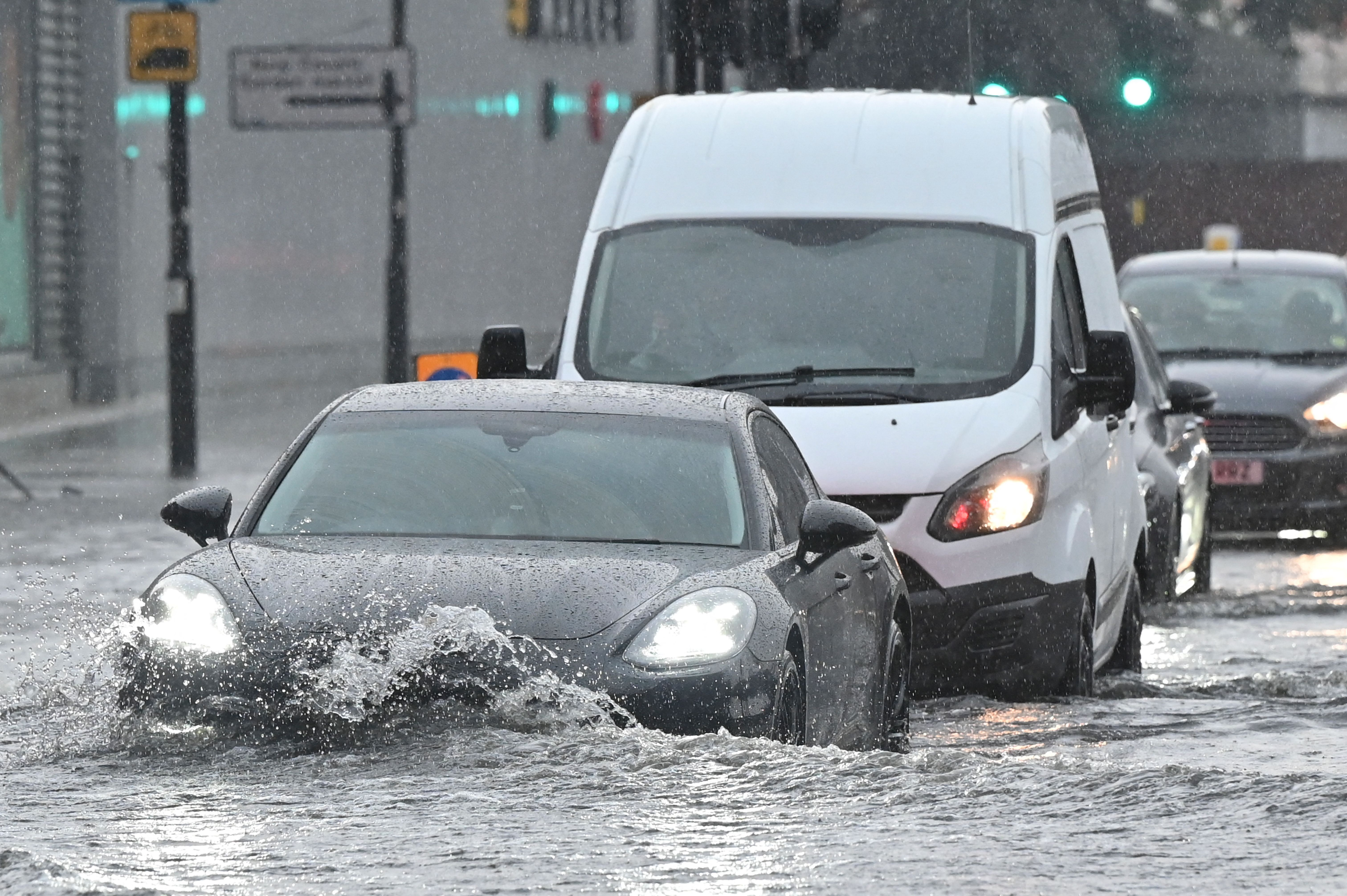 <p>Cars drive through deep water on a flooded road in The Nine Elms district of London on July 25, 2021 during heavy rain. - Buses and cars were left stranded when roads across London flooded on Sunday, as repeated thunderstorms battered the British capital. (Photo by JUSTIN TALLIS / AFP) (Photo by JUSTIN TALLIS/AFP via Getty Images)</p>