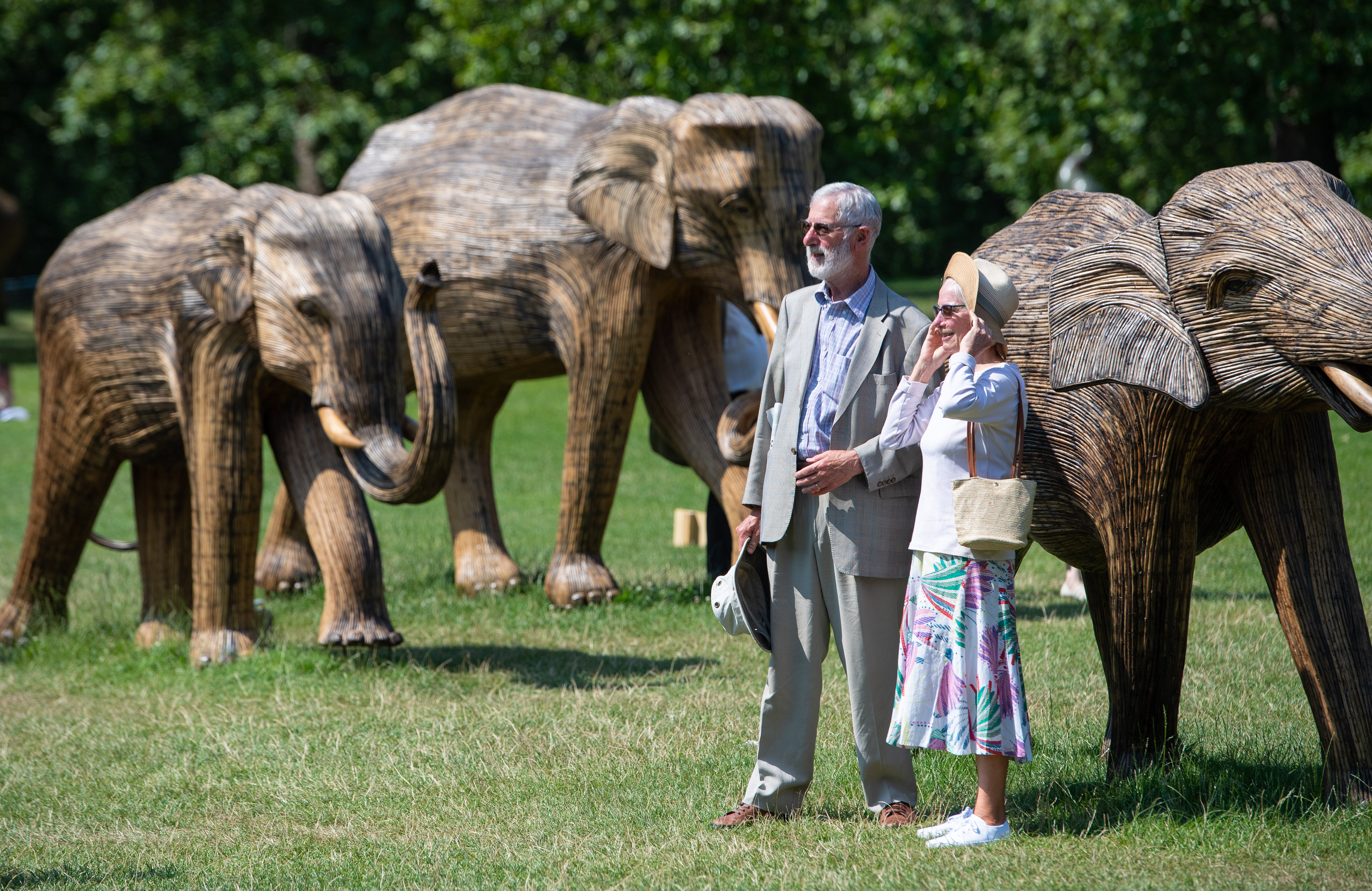 <p>A couple pose for a photo with one of the CoExistence elephant sculptures, as people enjoy the hot weather in Green Park, London. Temperatures are set to soar to sweltering highs this week after the Met Office issued an unprecedented heat warning. Picture date: Tuesday July 20, 2021.</p>