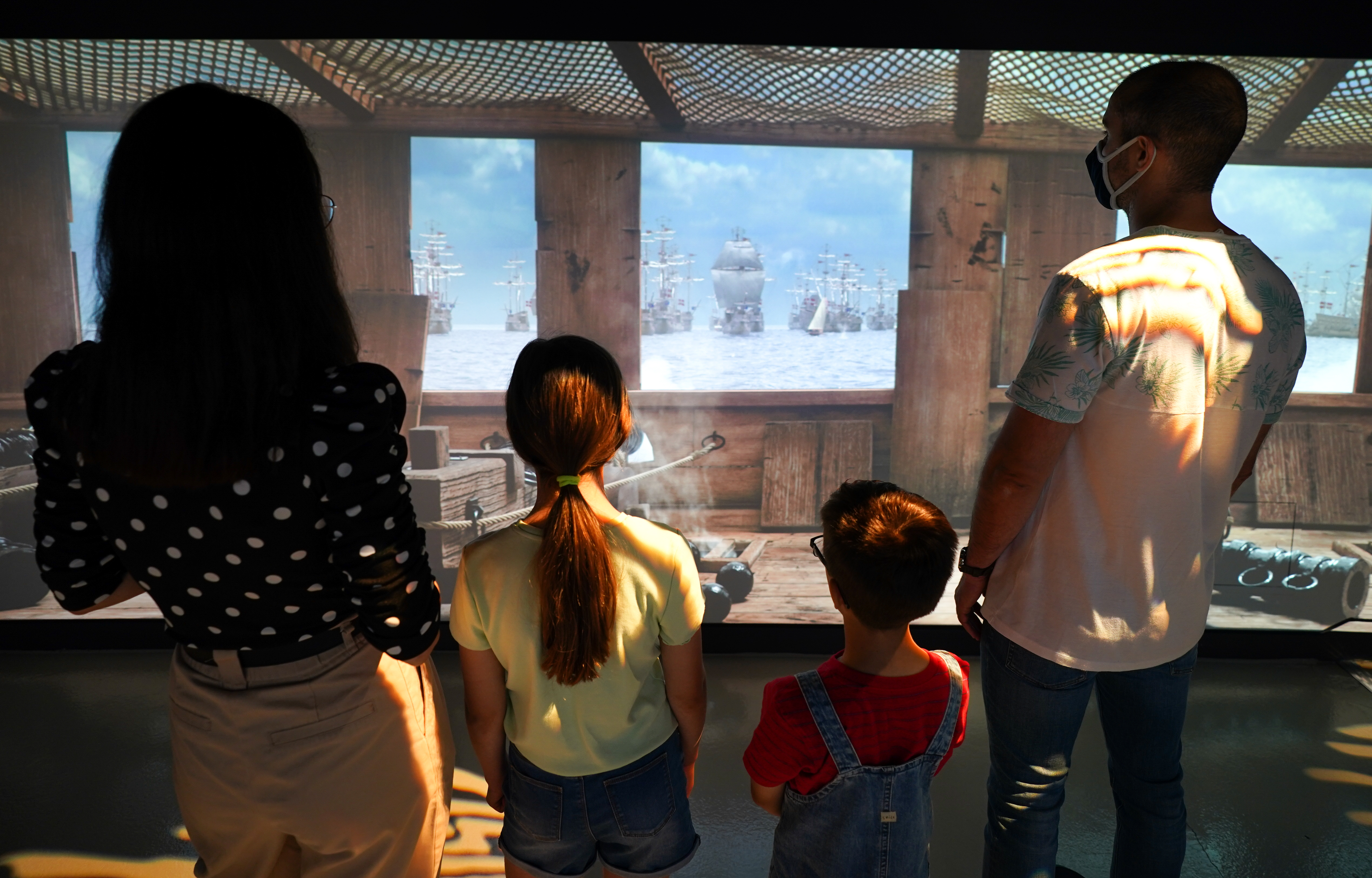 <p>A family watch a preview of the new 1545 experience at The Mary Rose exhibition at Portsmouth Historic Dockyard. Picture date: Wednesday July 14, 2021.</p>