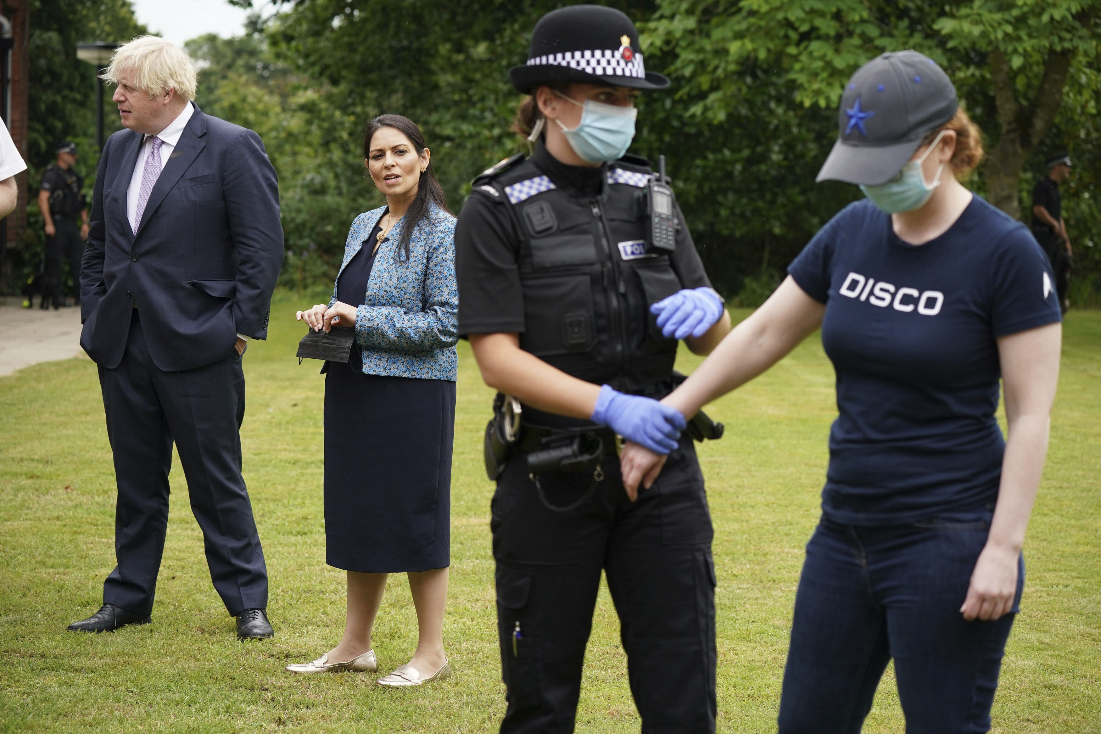 <p>Home Secretary Priti Patel, second left stands with Britain's Prime Minister Boris Johnson, as she watches a search exercise, during a visit to Surrey Police headquarters in Guildford, England, Tuesday July 27, 2021. (Yui Mok/Pool Photo via AP)</p>